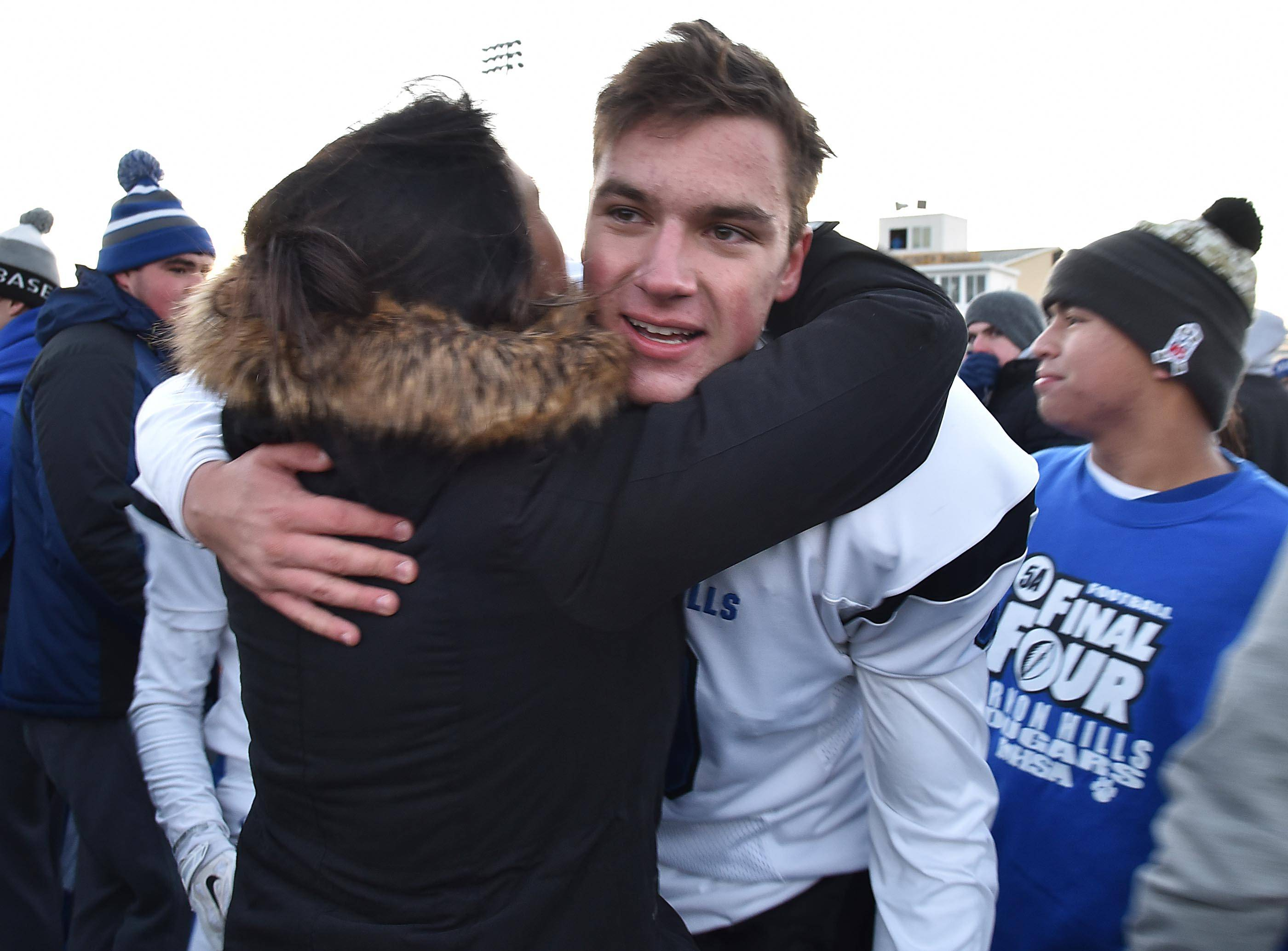 Vernon Hills kicker Andre Szmyt gets a hug after the Cougars defeated Sycamore on Saturday in the Class 5A football state semifinals.