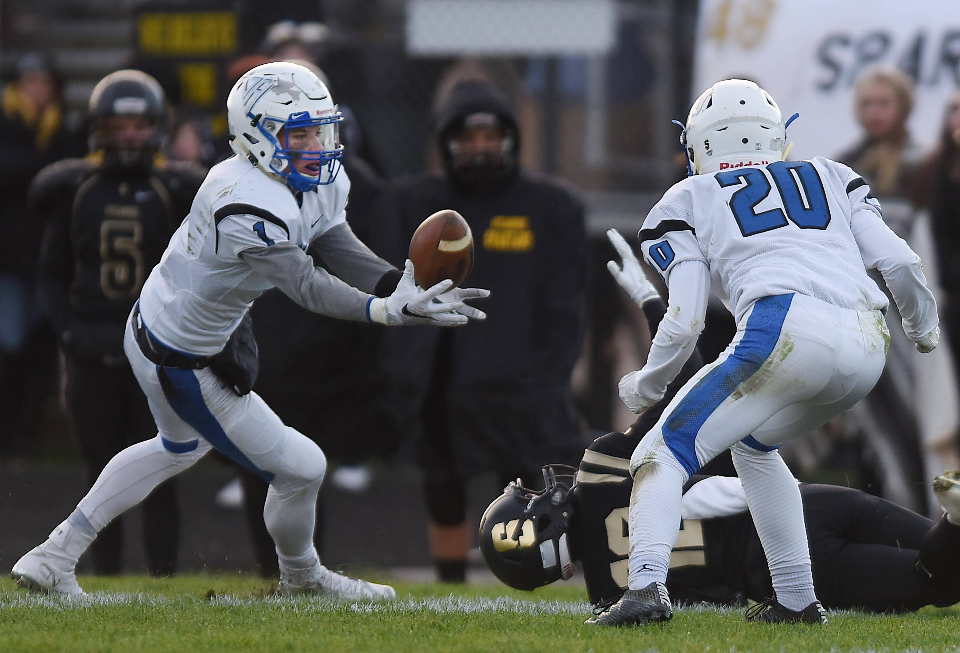 Vernon Hills' Chris Mariella grabs the live ball out of the air after teammate Jake Morris, right, tipped the pass away from Sycamore's Robert Cole, on the ground, in the final minutes Saturday in the Class 5A football state semifinals in Sycamore.