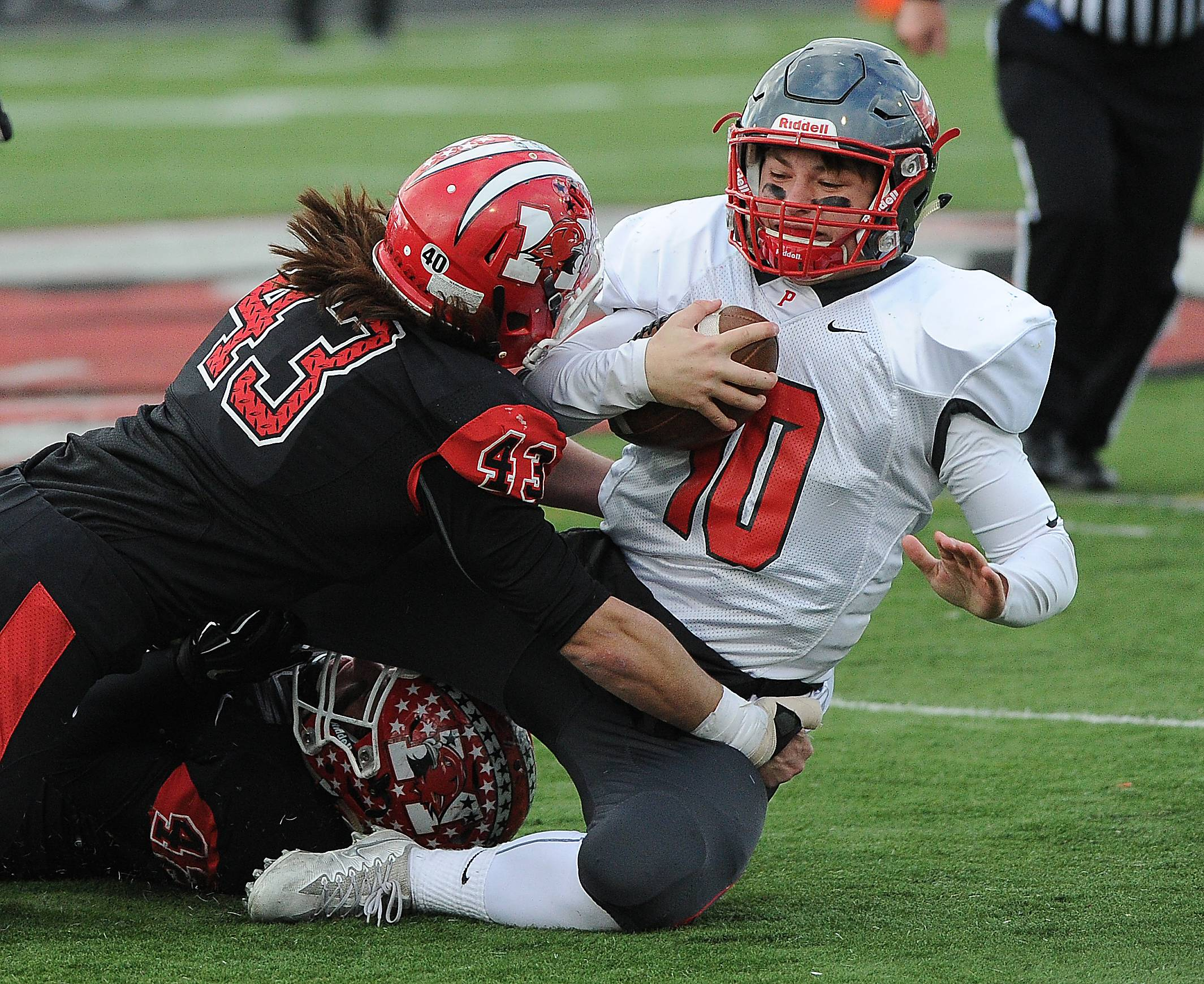 Palatine quarterback DJ Angelaccio gets jammed up by Maine South Mark Canizares in the first half in Park Ridge on Saturday.