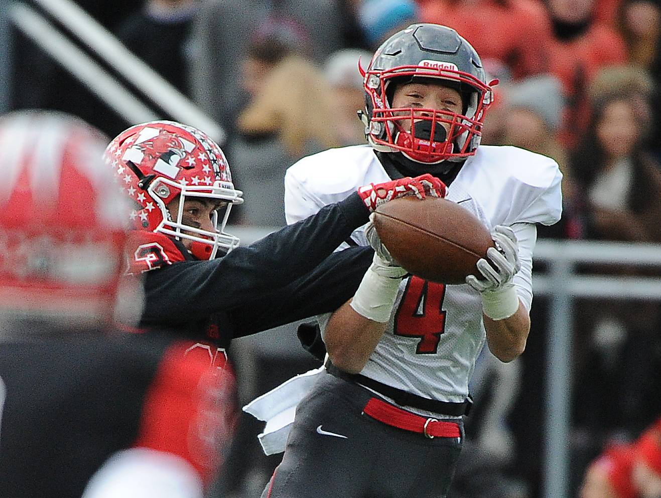 Palatine's Jack Orlando tries to hang on to pass, but Maine South's Matt Holbrook reaches to break it up in Class 8A semifinal play Saturday.