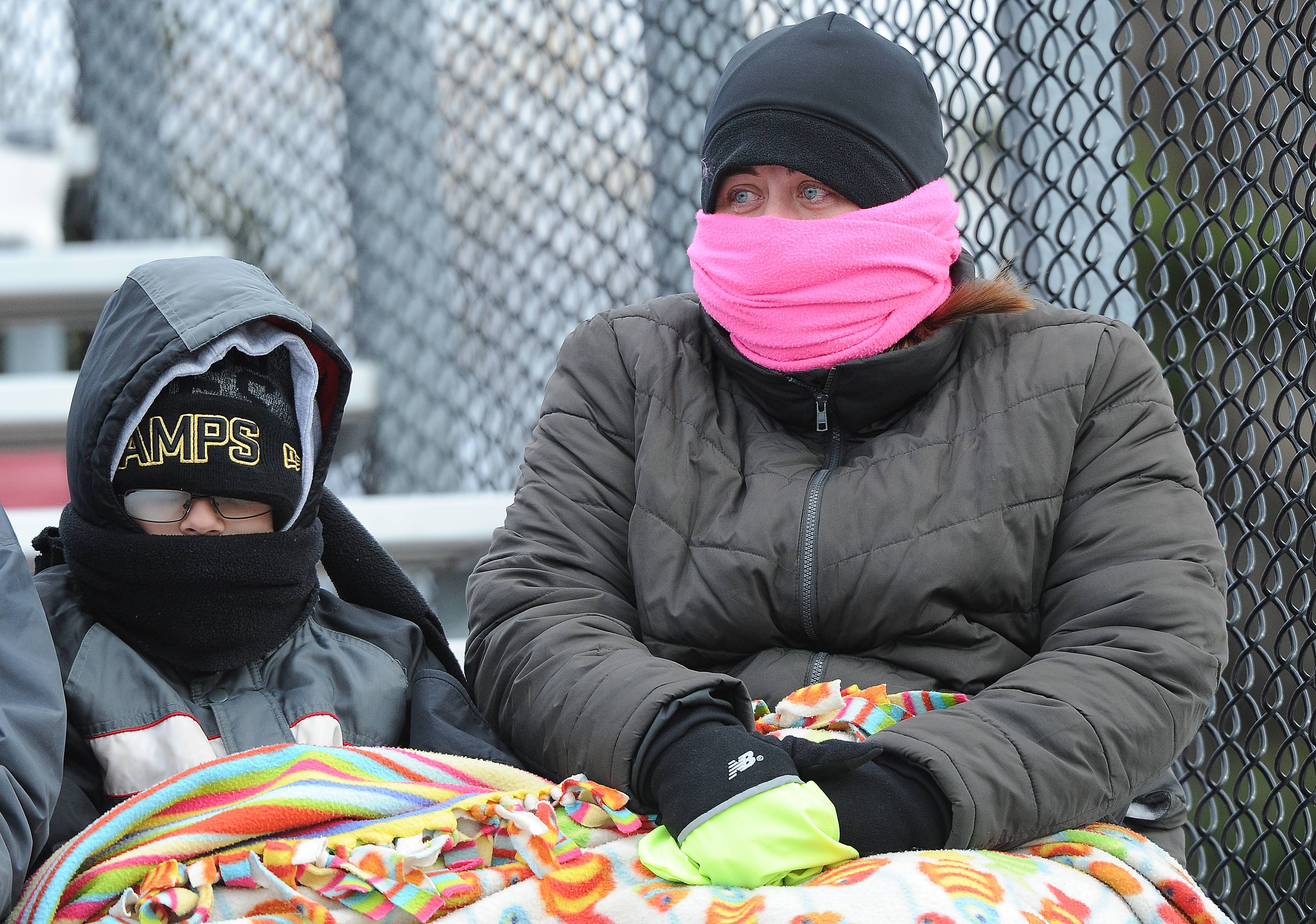 Beth Streicher and her son Nathan, of Lindenhurst, bundle up during Maine South's 28-14 victory over Palatine on Saturday in the Class 8A state semifinals.