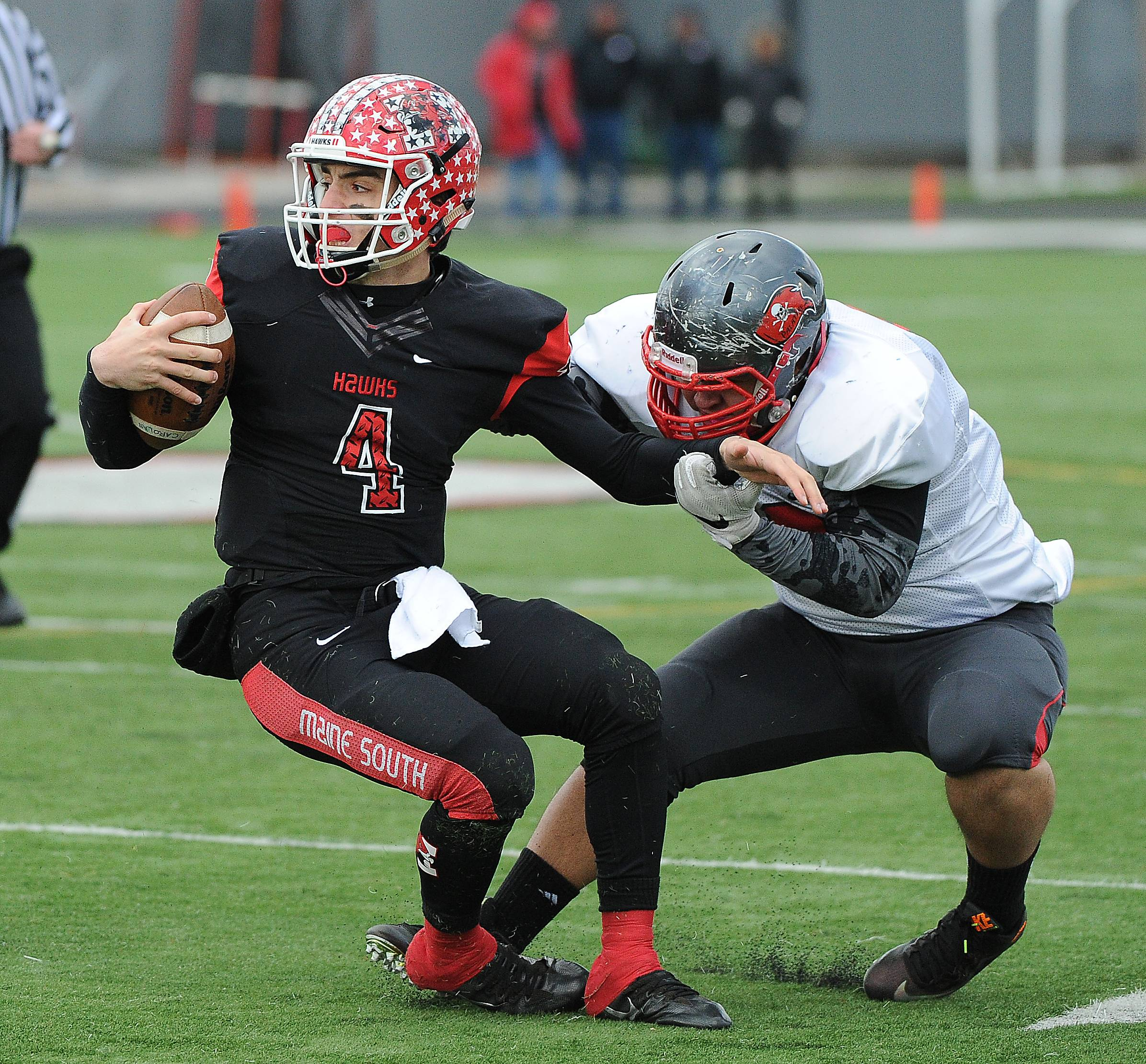 Palatine's defense tries to contain Maine South quarterback Nick Leongas in the first quarter on Saturday