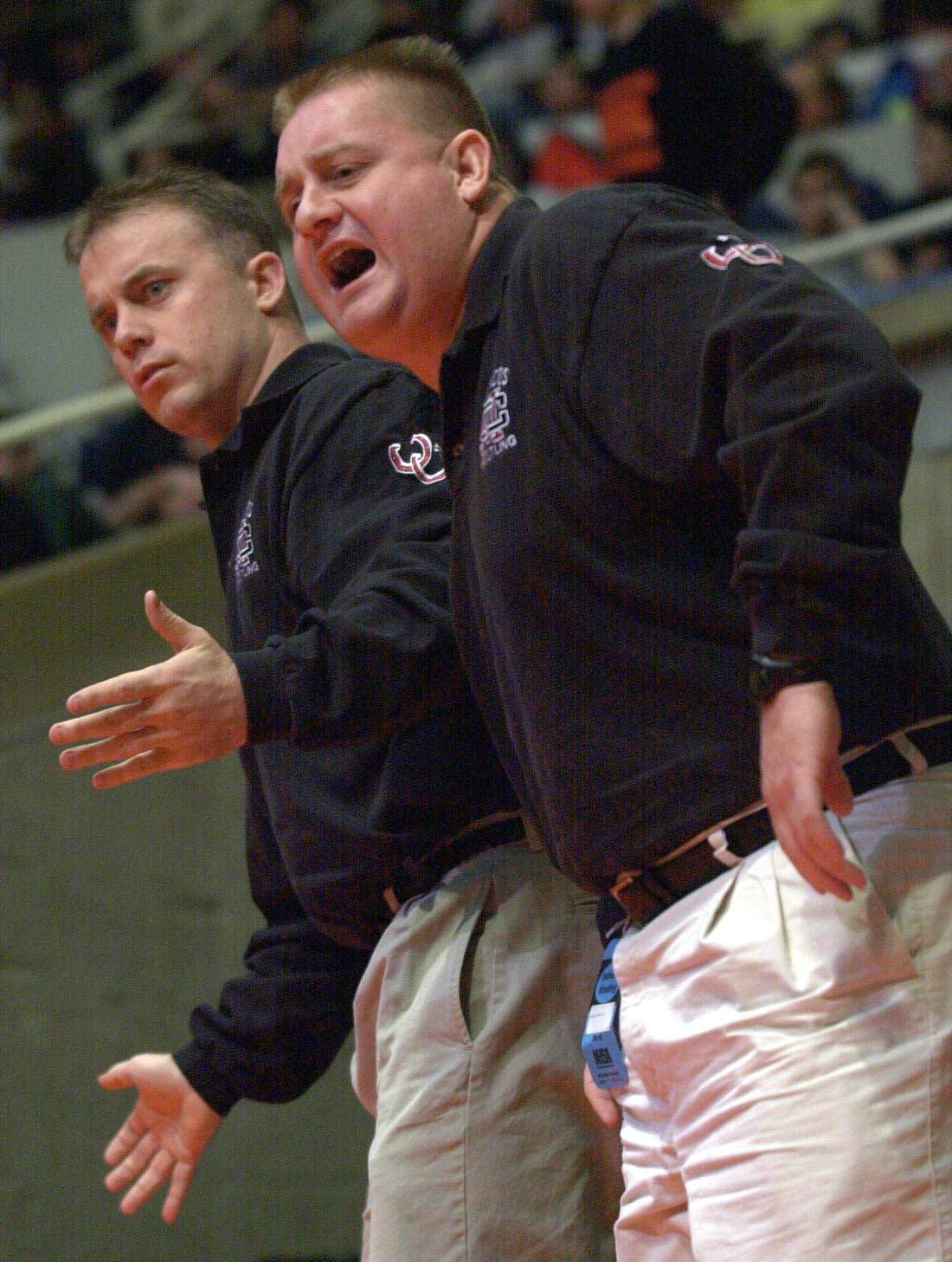 semis_2ps0216chach Photo0155390 hankins dupage Montini head coach Mike Bukovsky, front, coaches one of his wrestlers as assistant John Dziewiatkowski helps as well. Montini had a strong team showing with nine wrestlers in the semifinals Saturday.