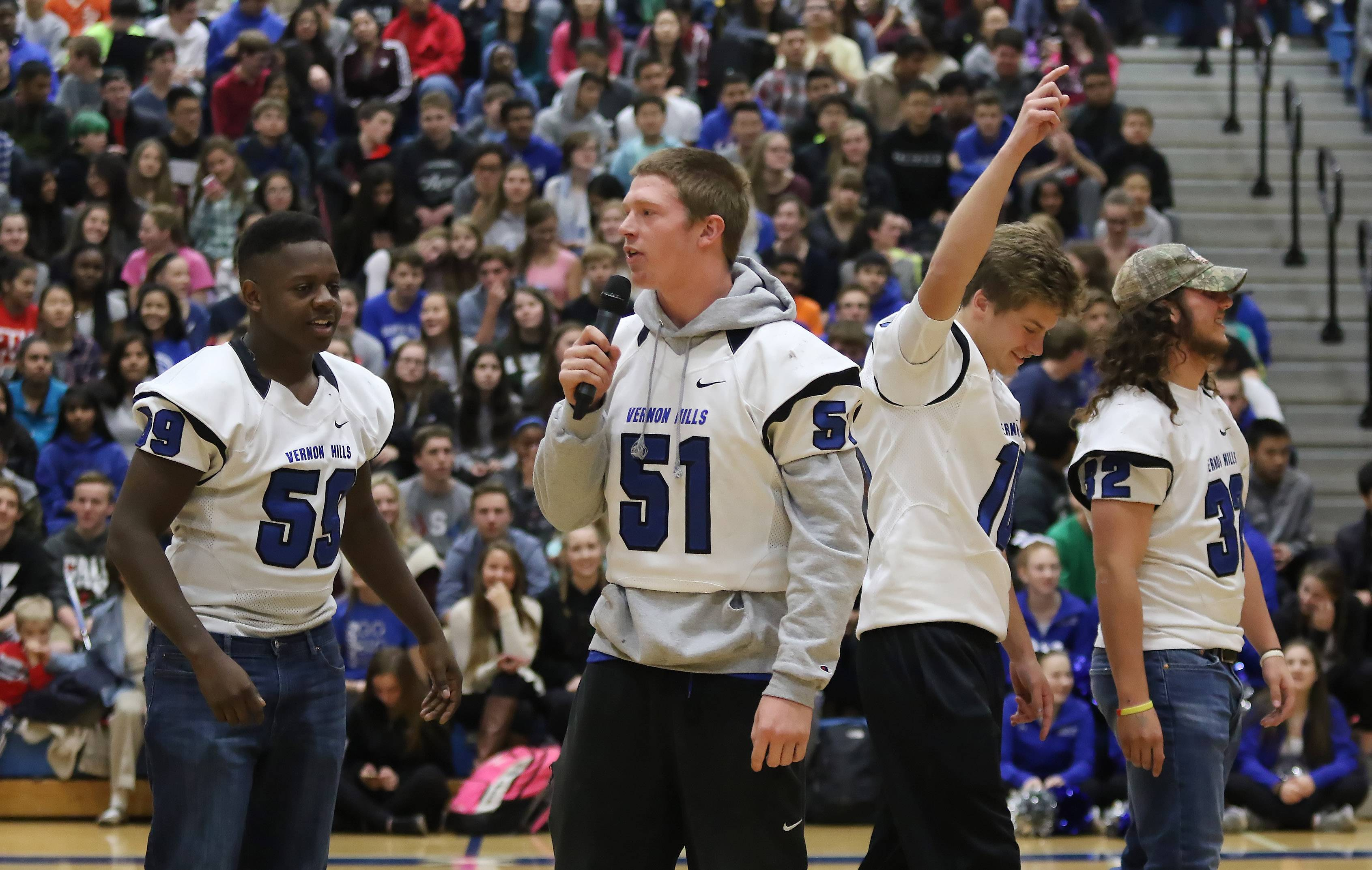 Vernon Hills High School football captains Mac Vincent, left, Andrew Smith, Kyle Hull and Jeffrey Rosenstock try to pump up the crowd during a pep rally Wednesday. The team will play for the Class 5A state football championship Saturday.