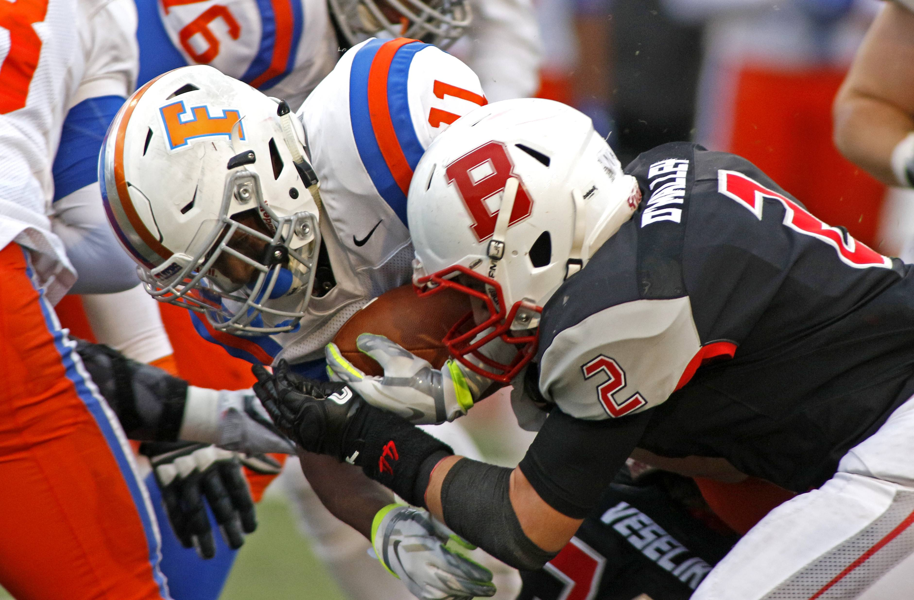 Benet Academy's Danny O'Malley (2) wraps up East St. Louis' Jigg Brown (11) during Class 7A semifinal playoff football action in Lisle. East St. Louis meets Plainfield North for the Class 7A championship on Saturday.