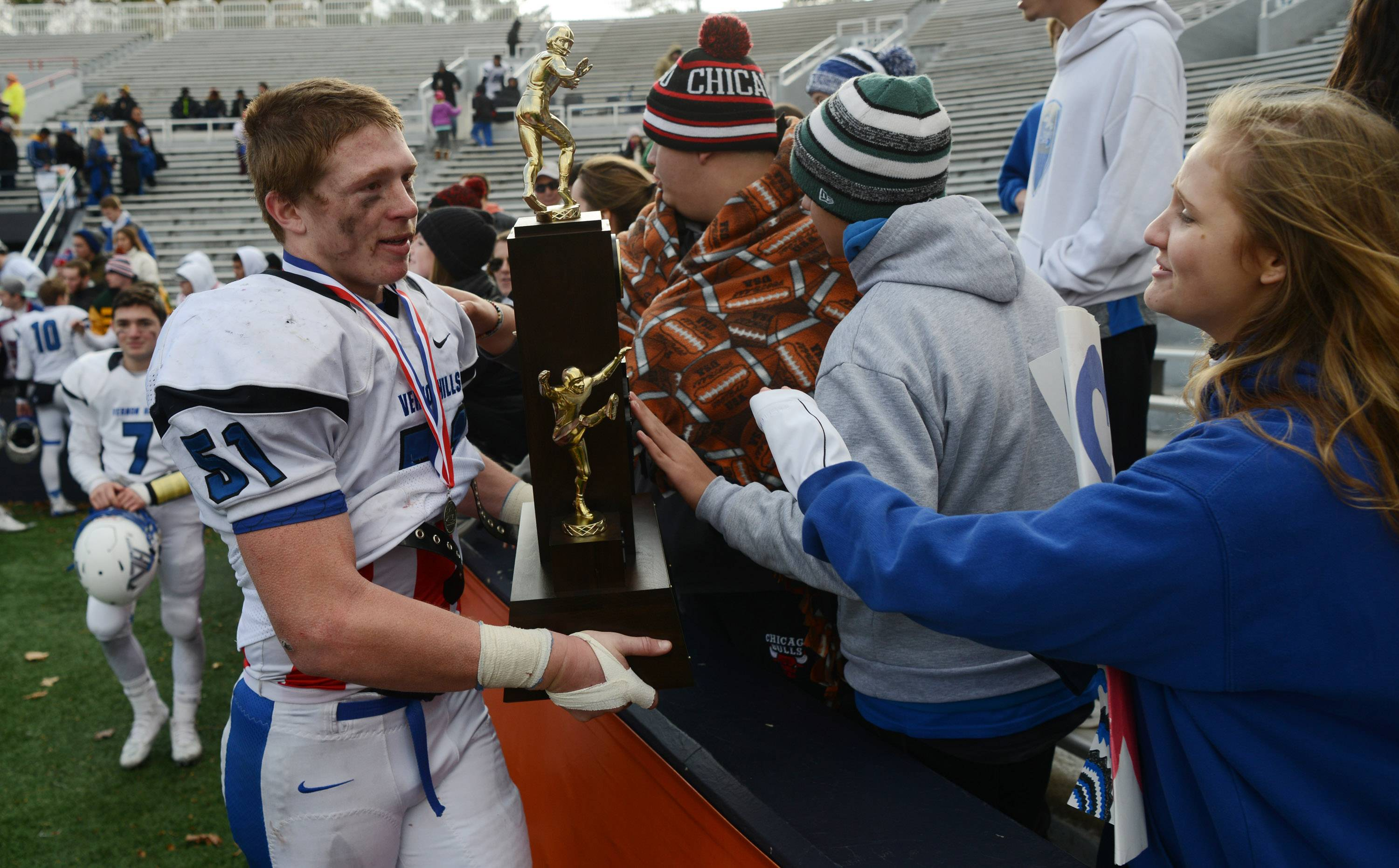Vernon Hills' Chick Smith shows the second-place trophy to fans following the Cougars' loss to Peoria in last weekend's Class 5A championship game at Memorial Stadium in Champaign.