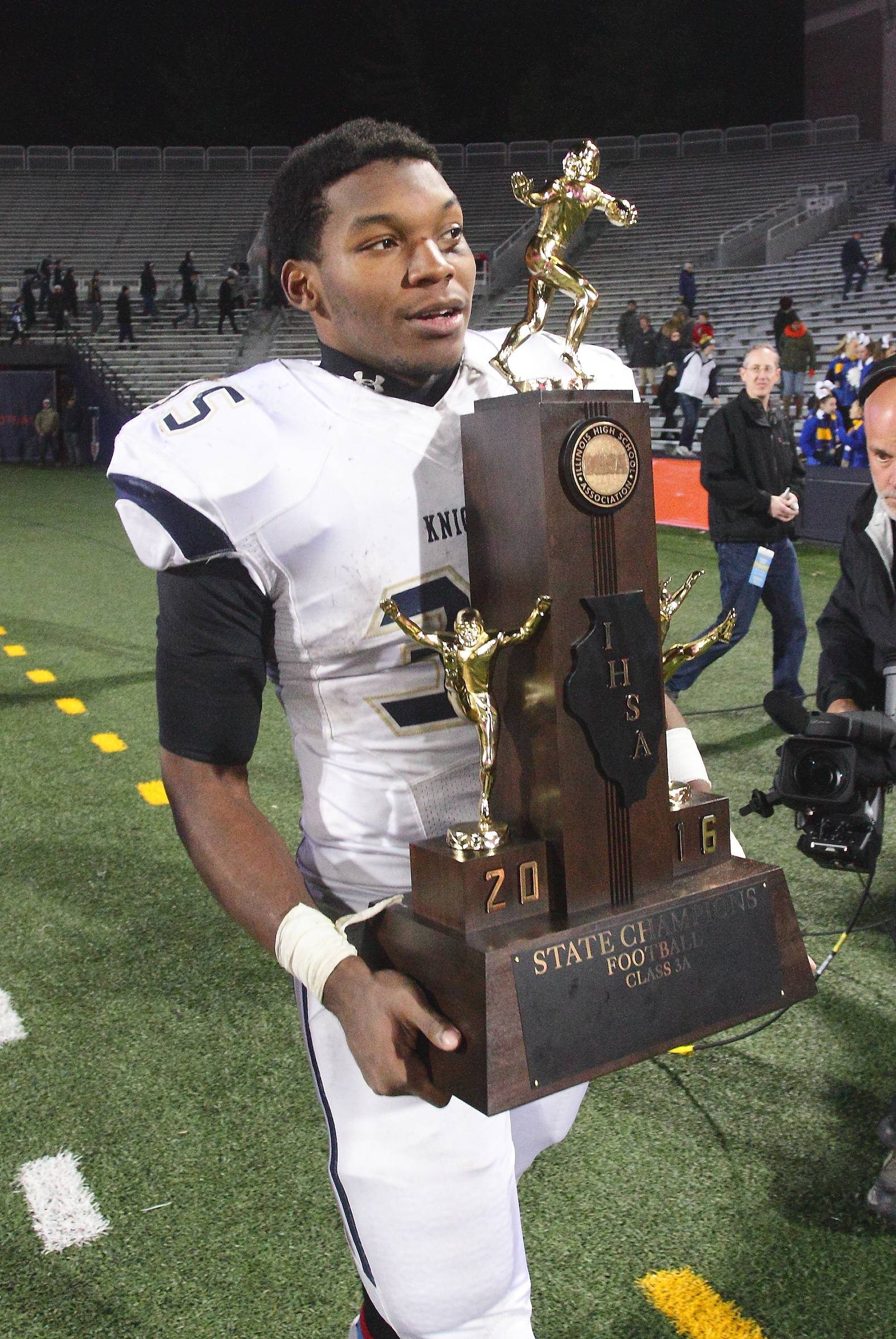 IC Catholic Prep's Jordan Rowell carries the team's championship trophy after the IHSA Class 3A football award ceremony. The Knights blanked the Cavaliers 43-0 to win this year's title.