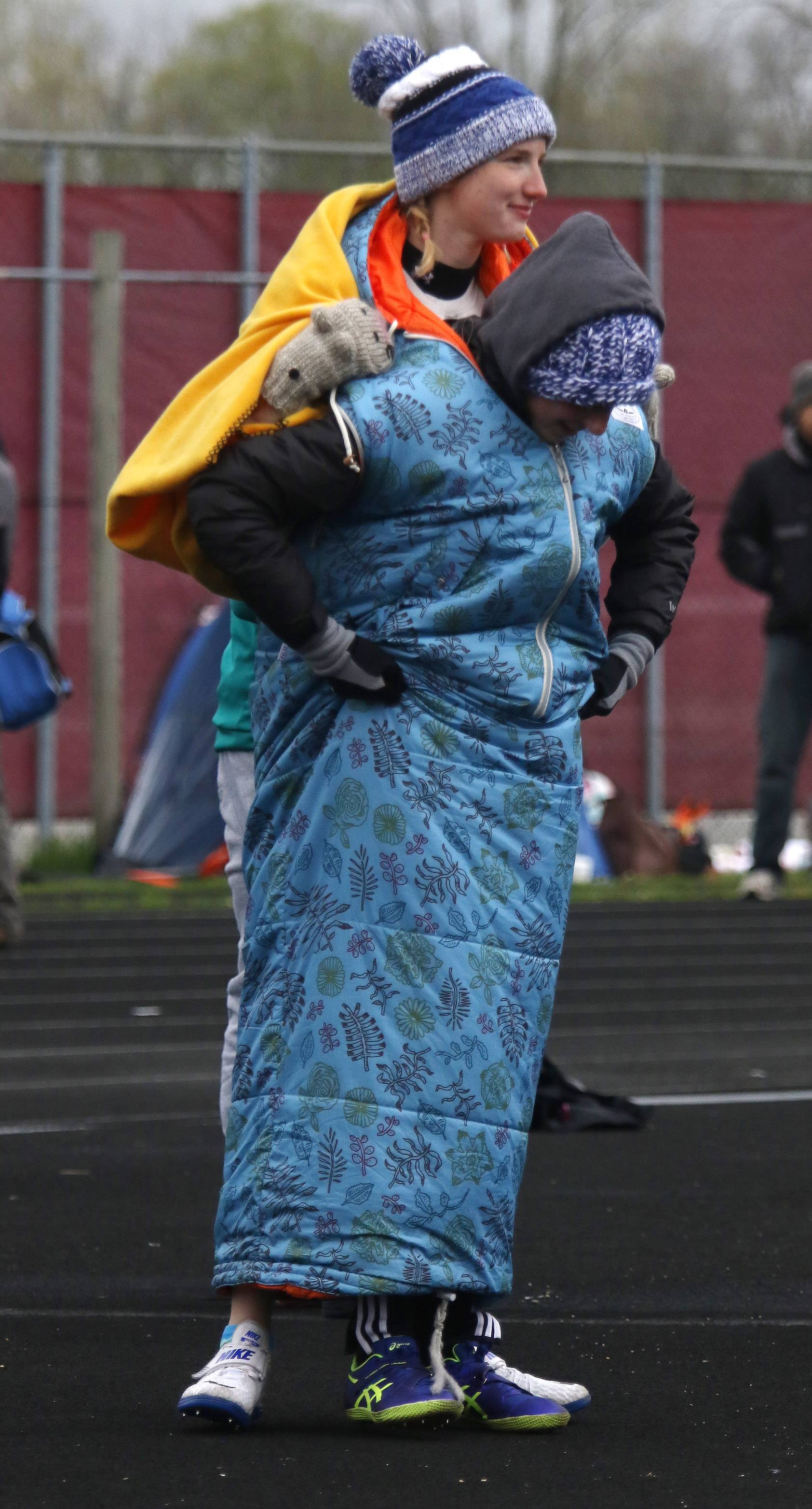 Lake Zurich athletes Kendall Kearnan, back, and Mackenzie Weider keep warm by walking around in the same sleeping bag during the Lake County girls track meet Thursday at Deerfield.