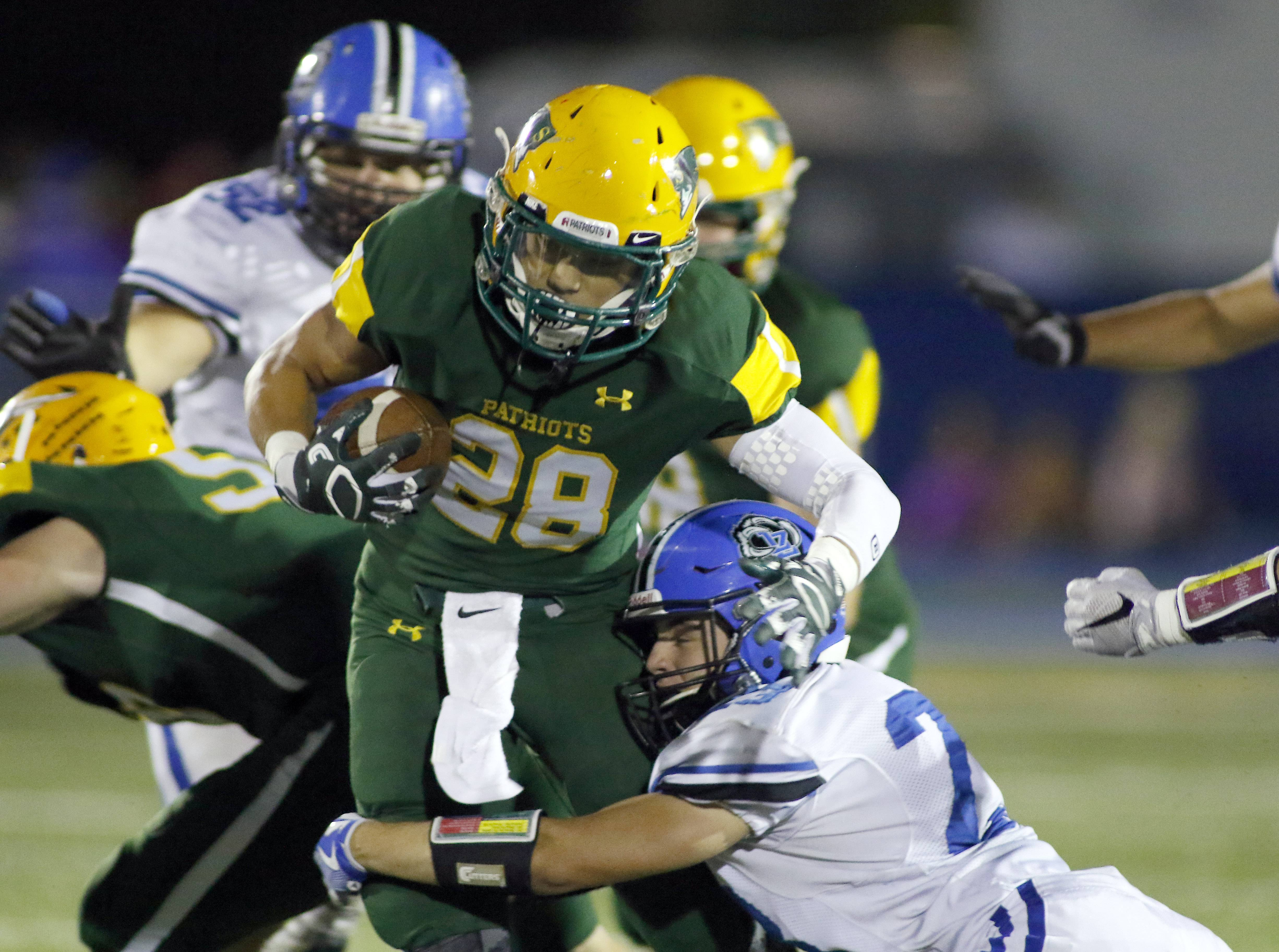 Stevenson High's Matt Korinek (28) tries to slide through a tackle against Lake Zurich in a 2016 game. Under a new contract, all varsity athletes at Stevenson High will wear uniforms manufactured by Under Armour.