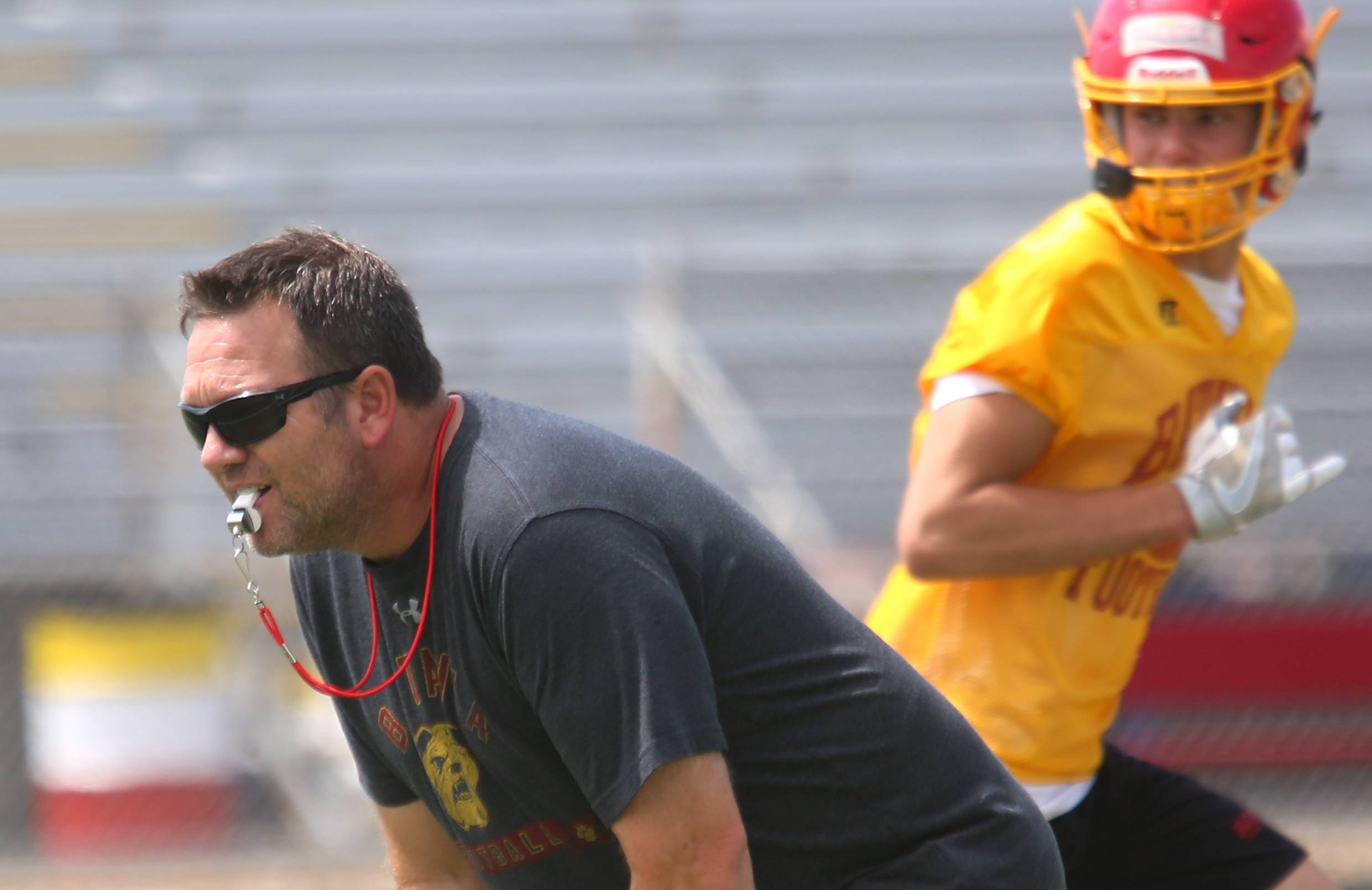 Head coach Dennis Piron keeps his eyes on the action during the first day of the varsity practice season for Batavia High School football at Bulldog Stadium in Batavia Monday.