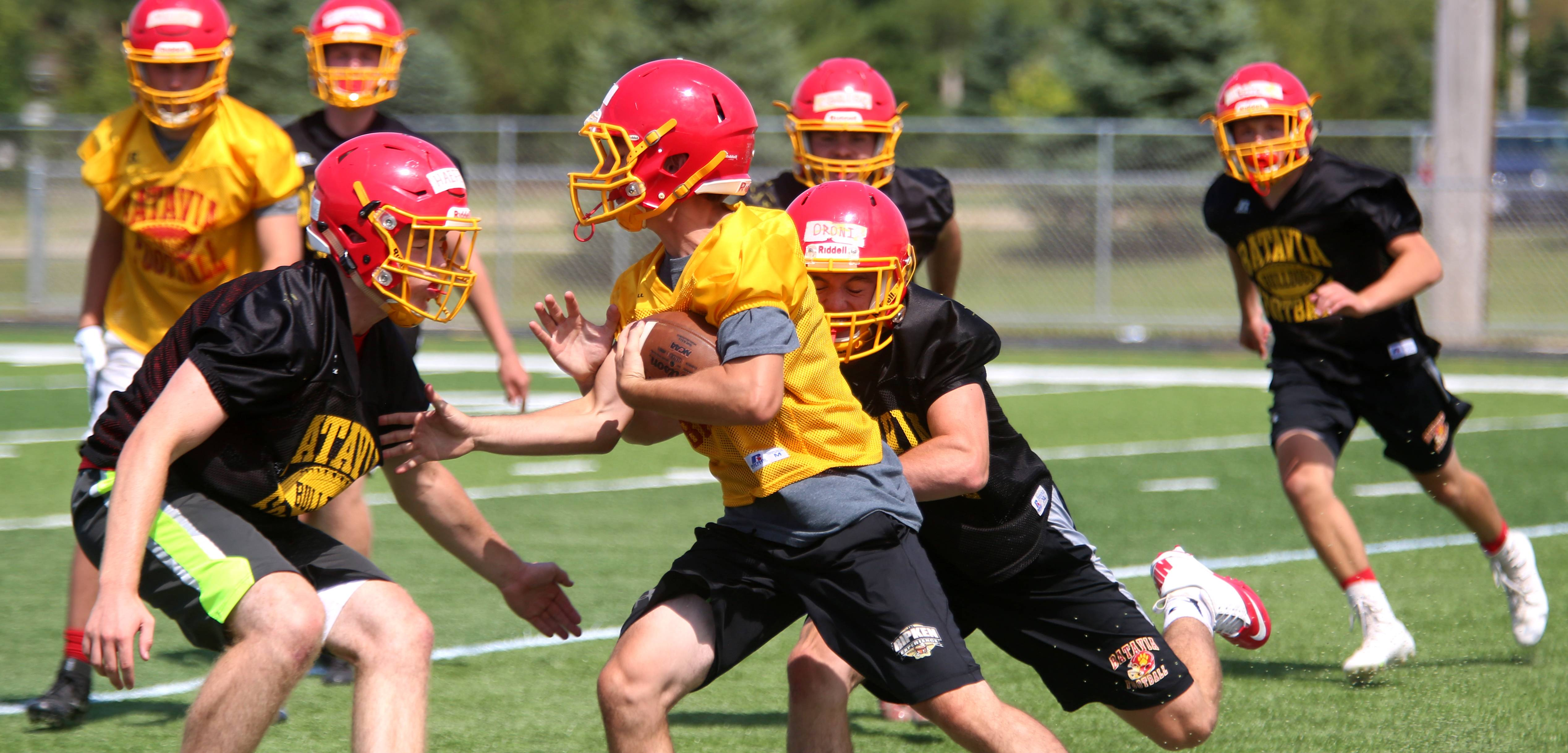 Players run through drills during the first day of the varsity practice season for Batavia High School football at Bulldog Stadium in Batavia Monday.