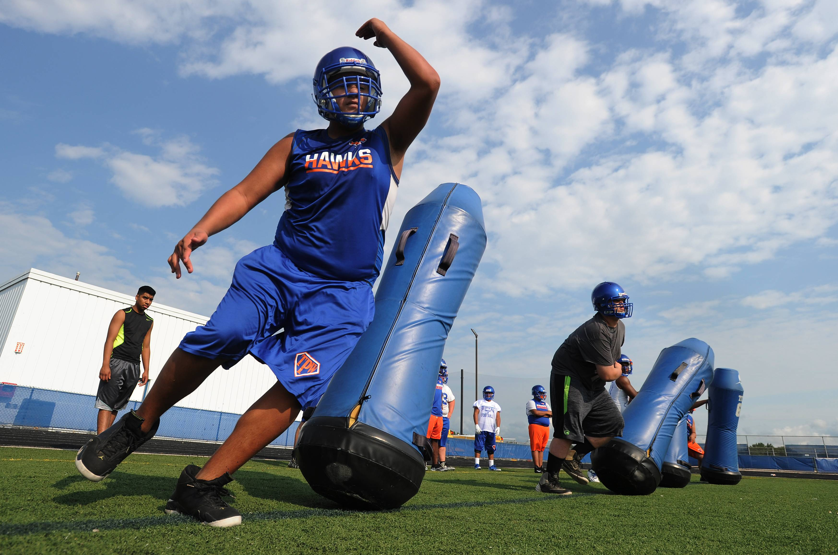 Hoffman Estates' Marco Bustos practices his defensive moves as day one of the high school football season kicks off at Hoffman Estates High School on Monday.