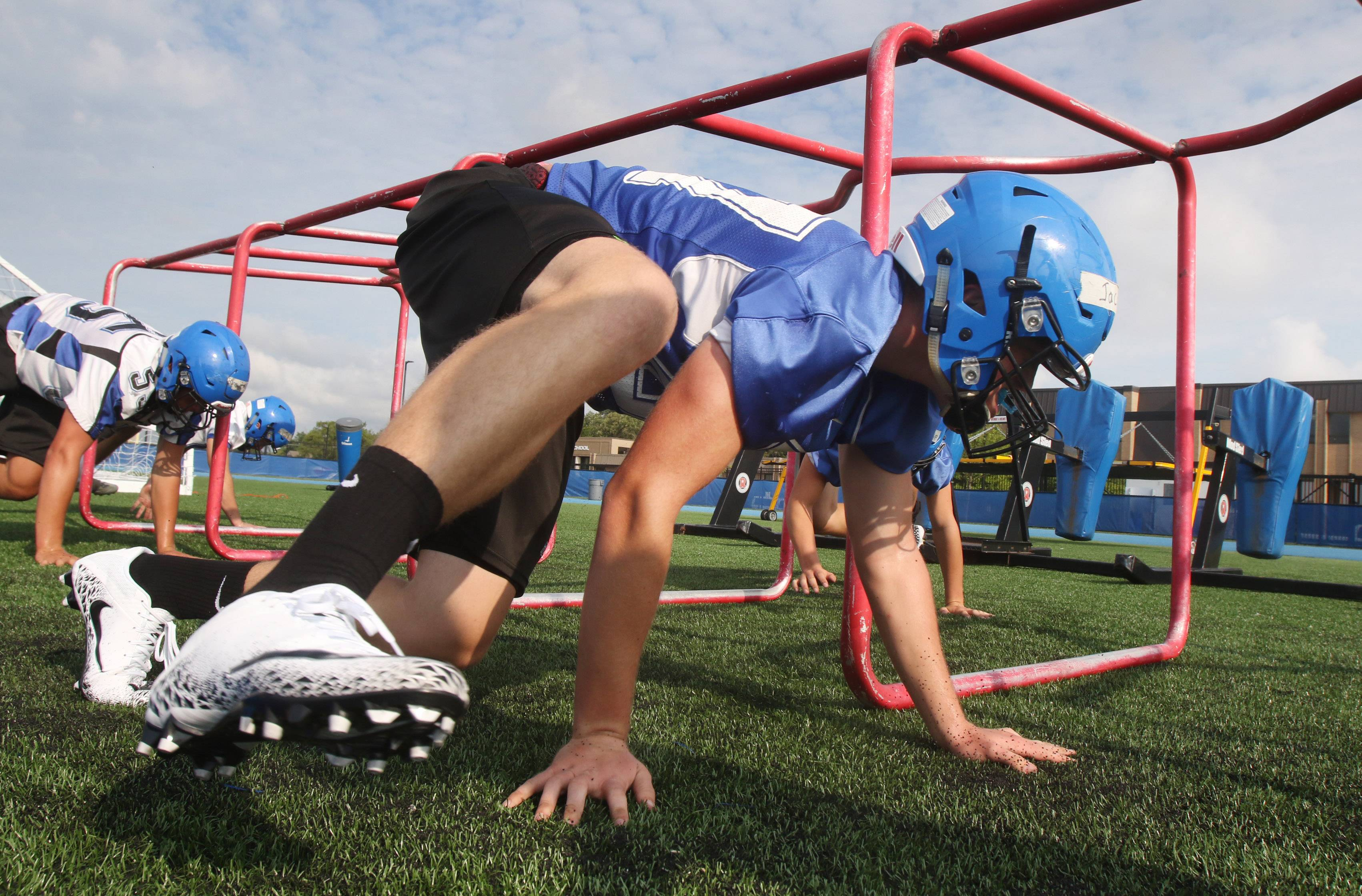 Jacob Davis crawls during drills on the first day of football practice at Lake Zurich High School on Monday.