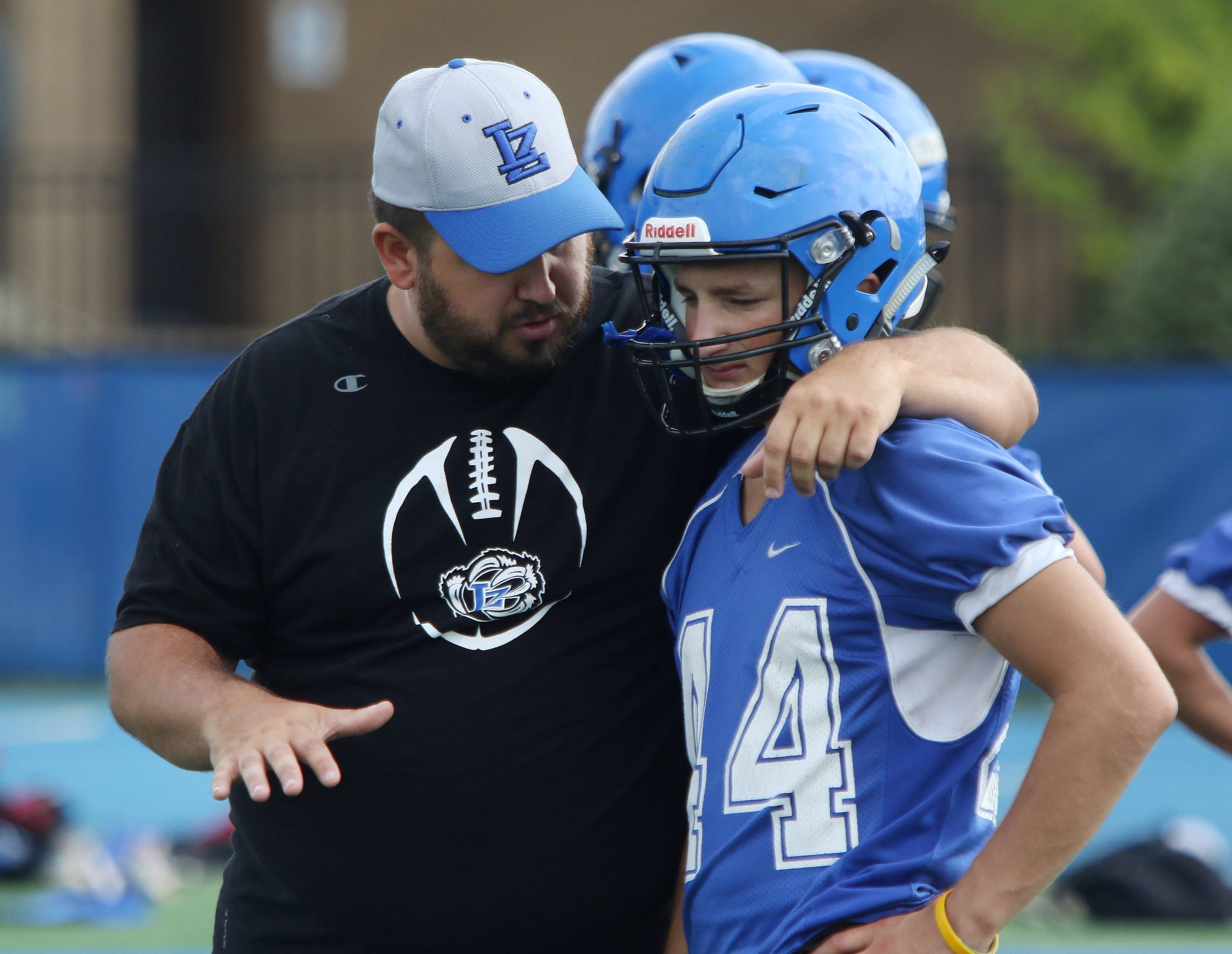Defensive coordinator Nicholas Summers talks to cornerback Austin LePage during the first day of football practice at Lake Zurich High School on Monday.