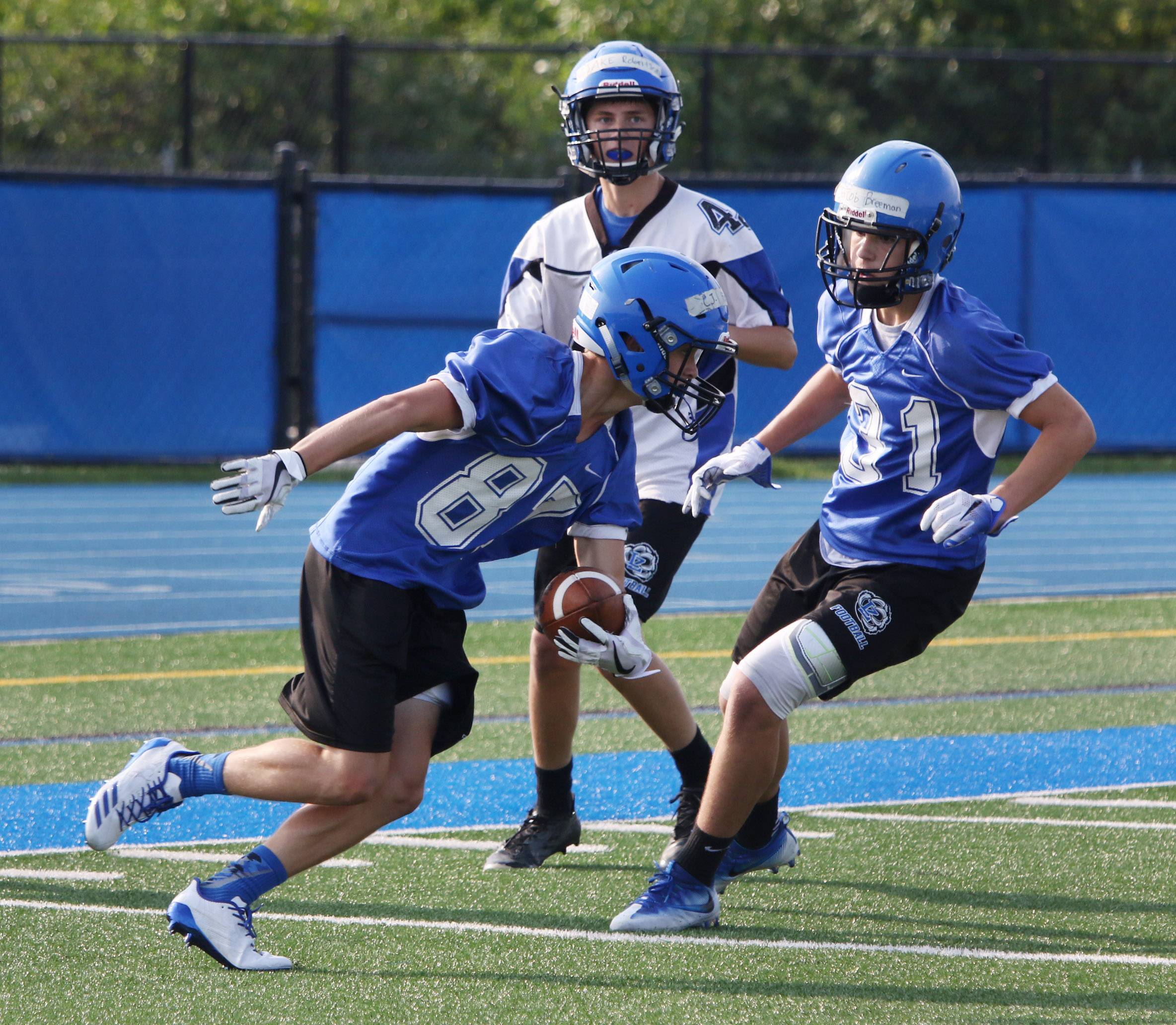 Wide receiver C.J. Holder runs around Jacob Breeman, right, after catching the ball during the first day of football practice at Lake Zurich High School on Monday.