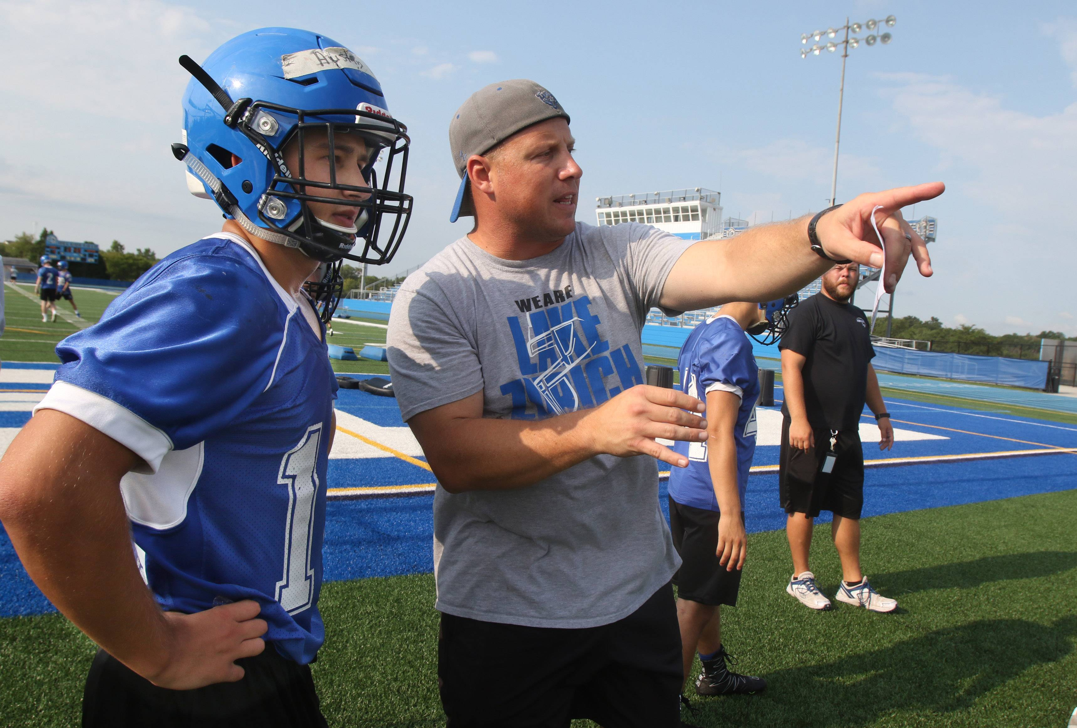 Assistant running backs coach Nate Boekholder talks with running back Austin LePage during the first day of football practice at Lake Zurich High School on Monday.