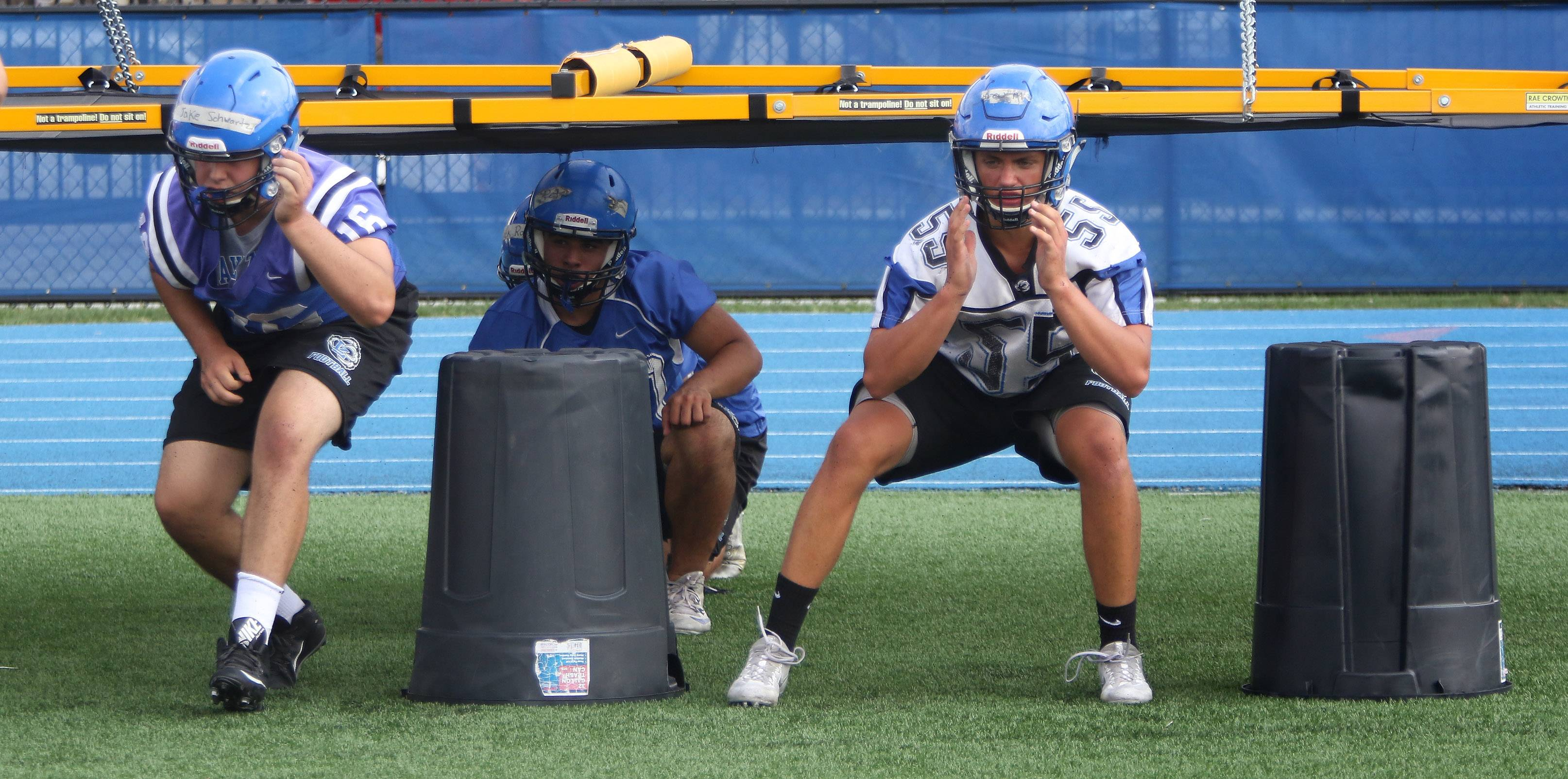 Jake Schwartz, left, and Andrew Miller go through blocking drills during the first day of football practice at Lake Zurich High School on Monday.