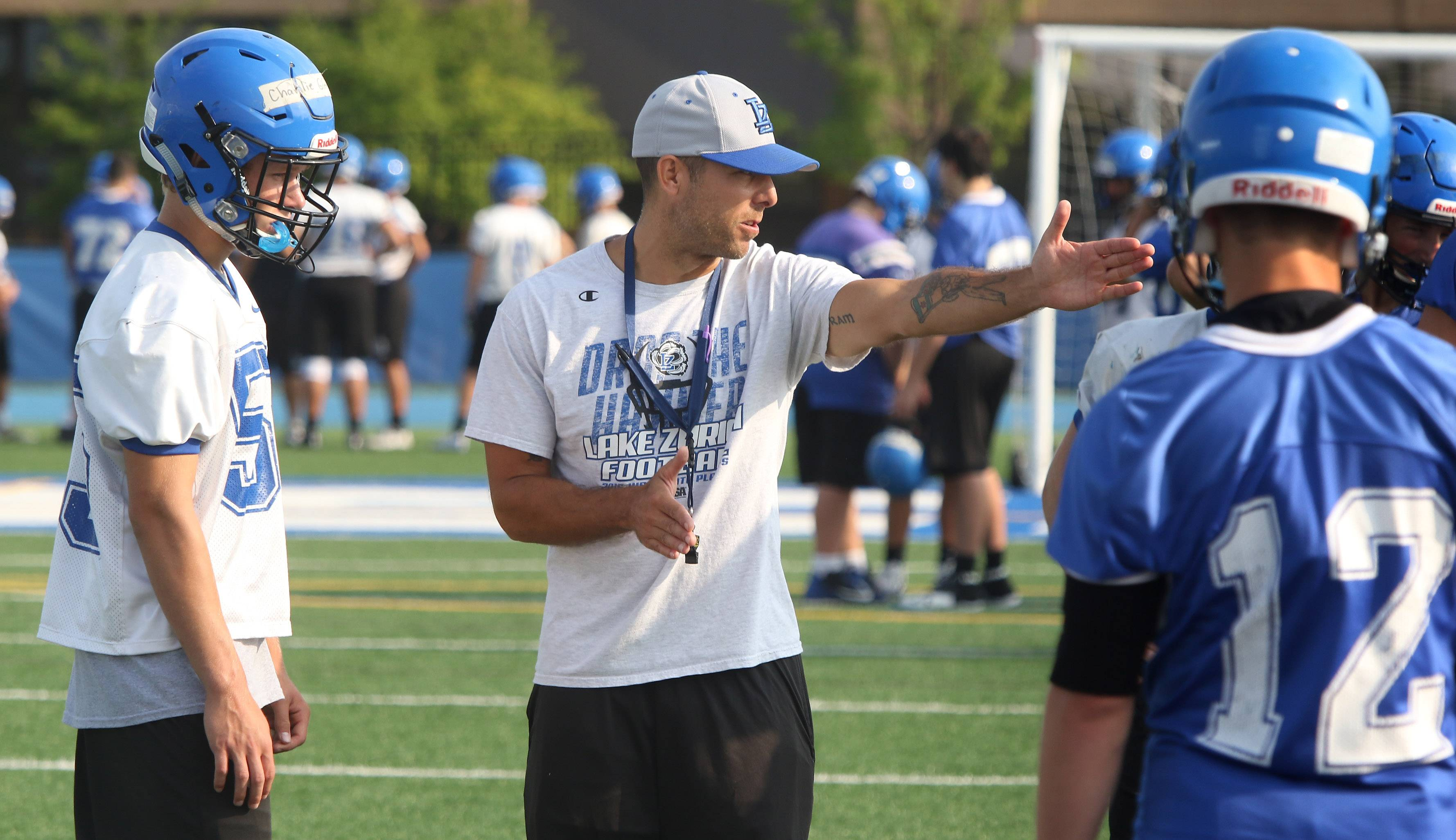 Head coach Luke Mertens directs his players during the first day of football practice at Lake Zurich High School on Monday.