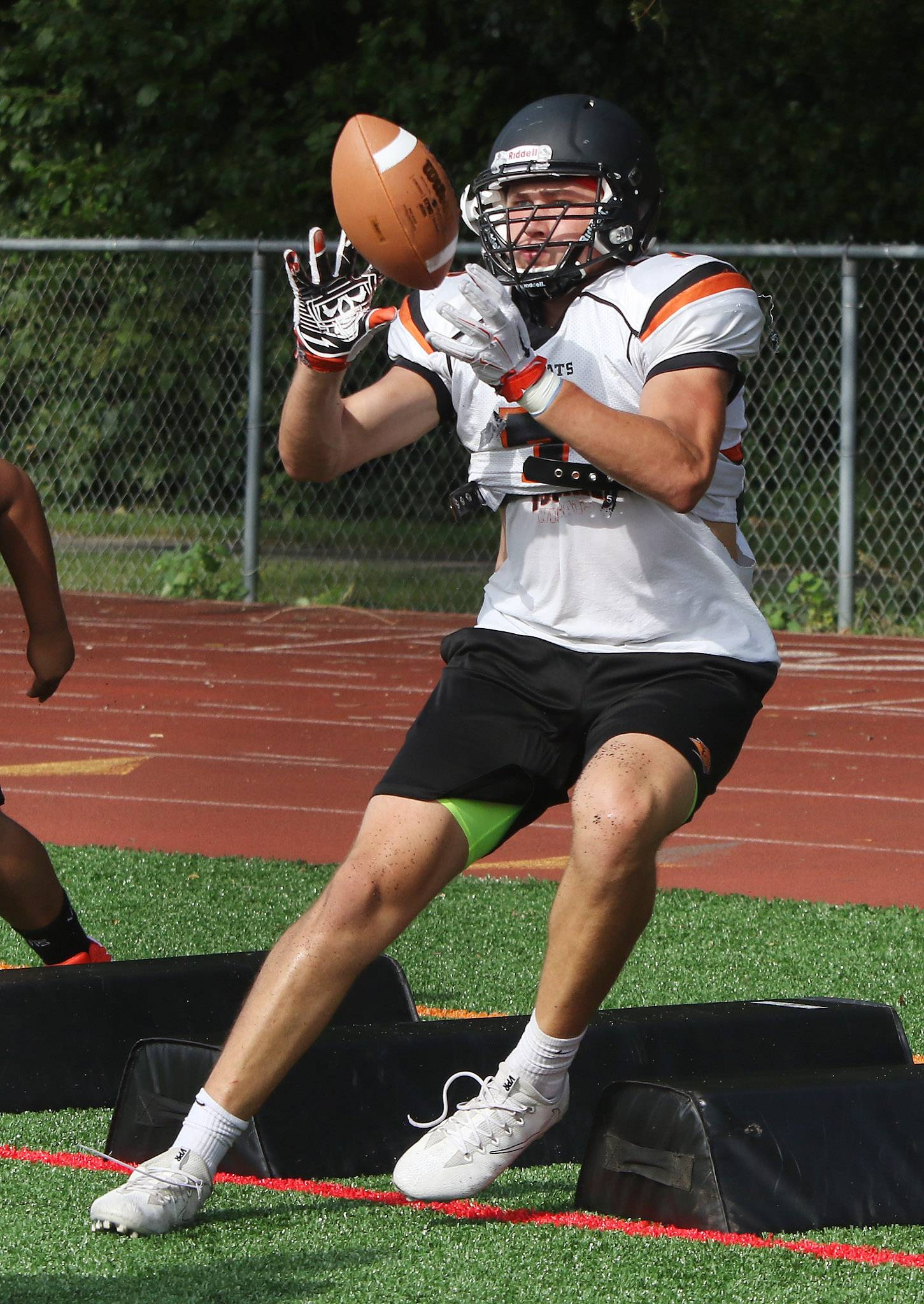 Brendan Cook catches the ball in drills during football practice at Libertyville.