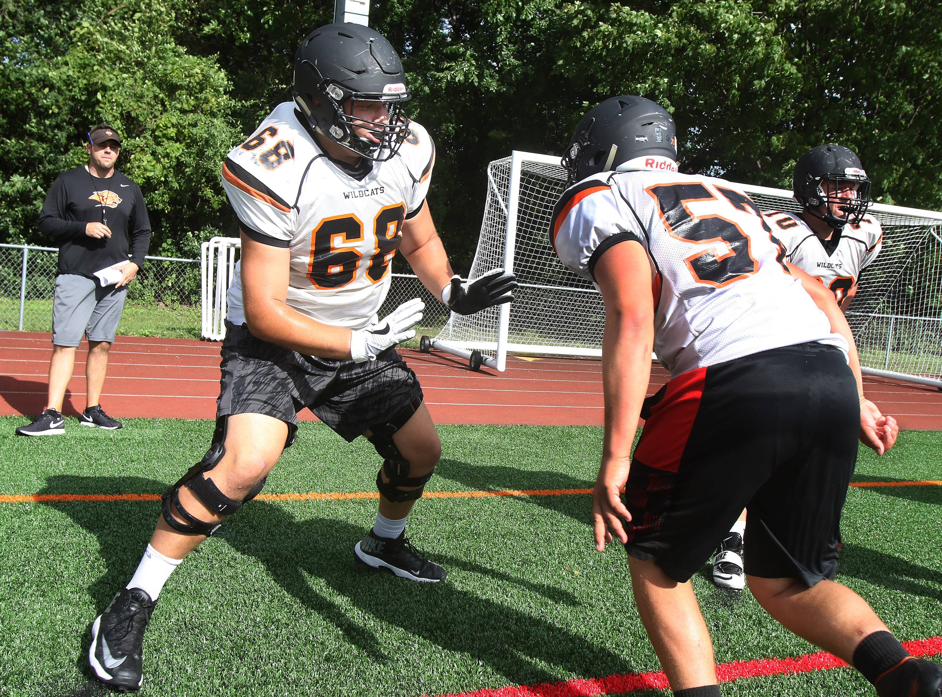 Offensive lineman Charlie Schmidt, left, blocks Bryan Bystol in a drill during football practice at Libertyville.