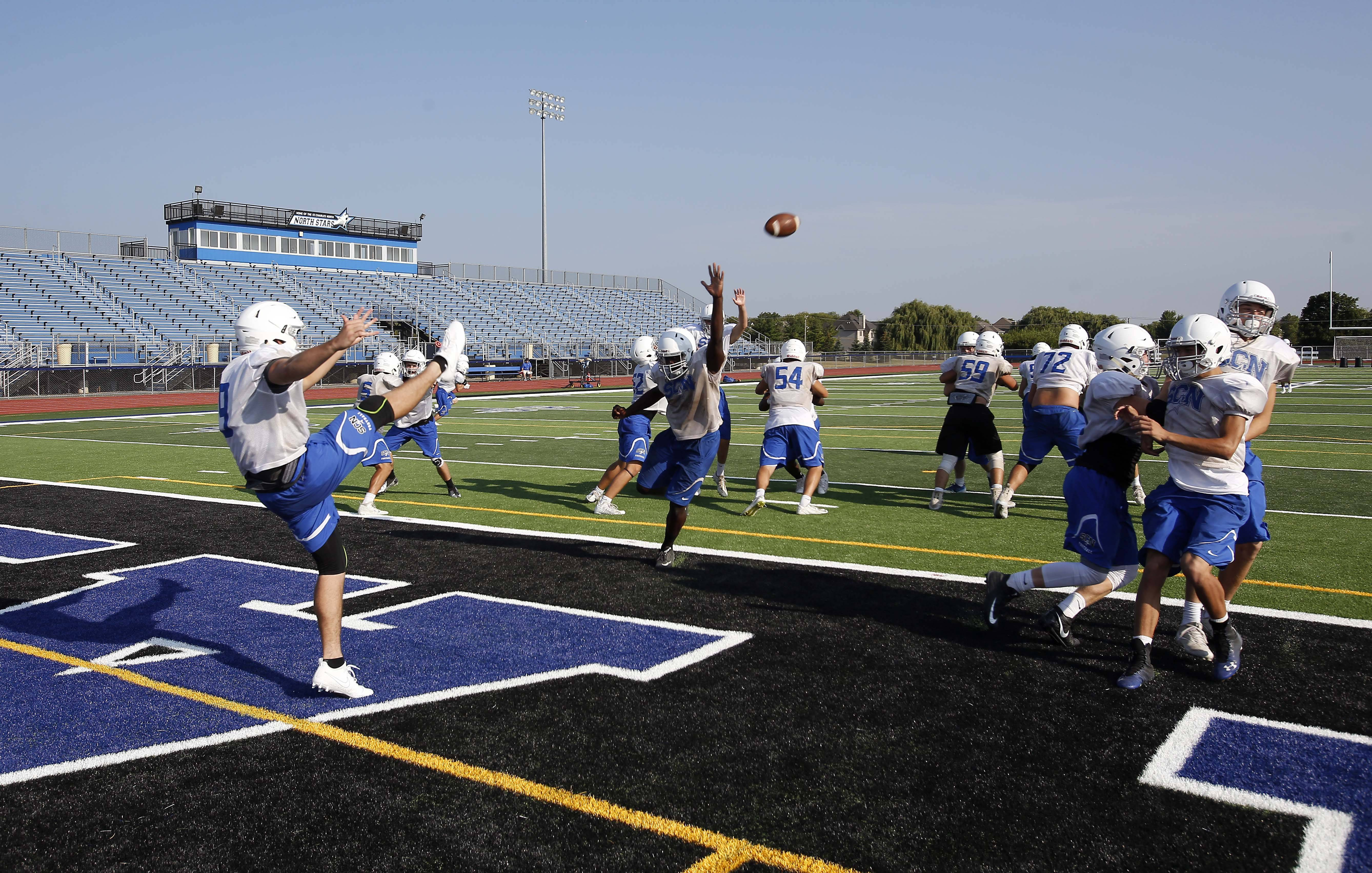 Mike Hohensee punts the football during St. Charles North football practice.