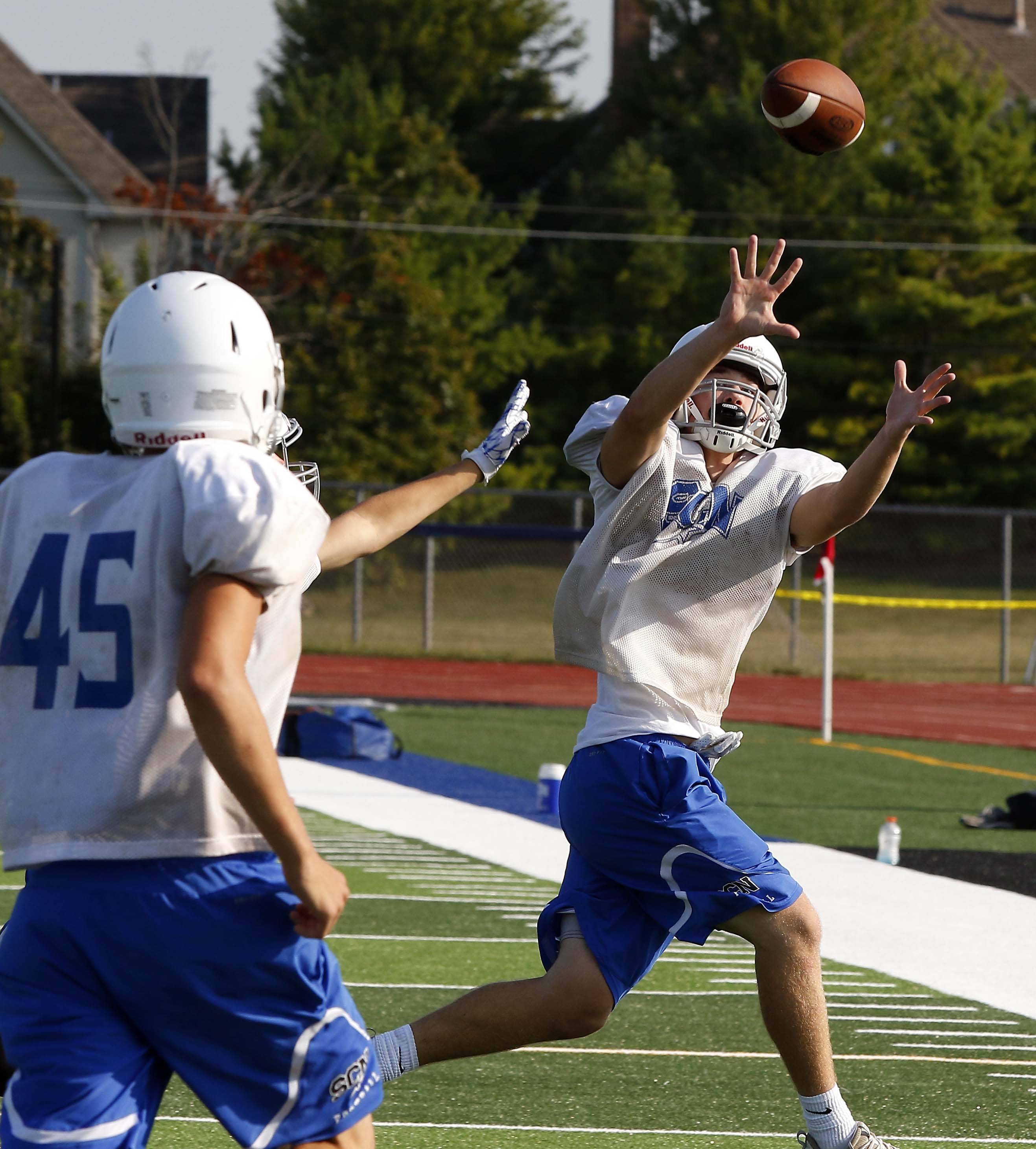 Hunter Molnar reels in a long pass during St. Charles North football practice.