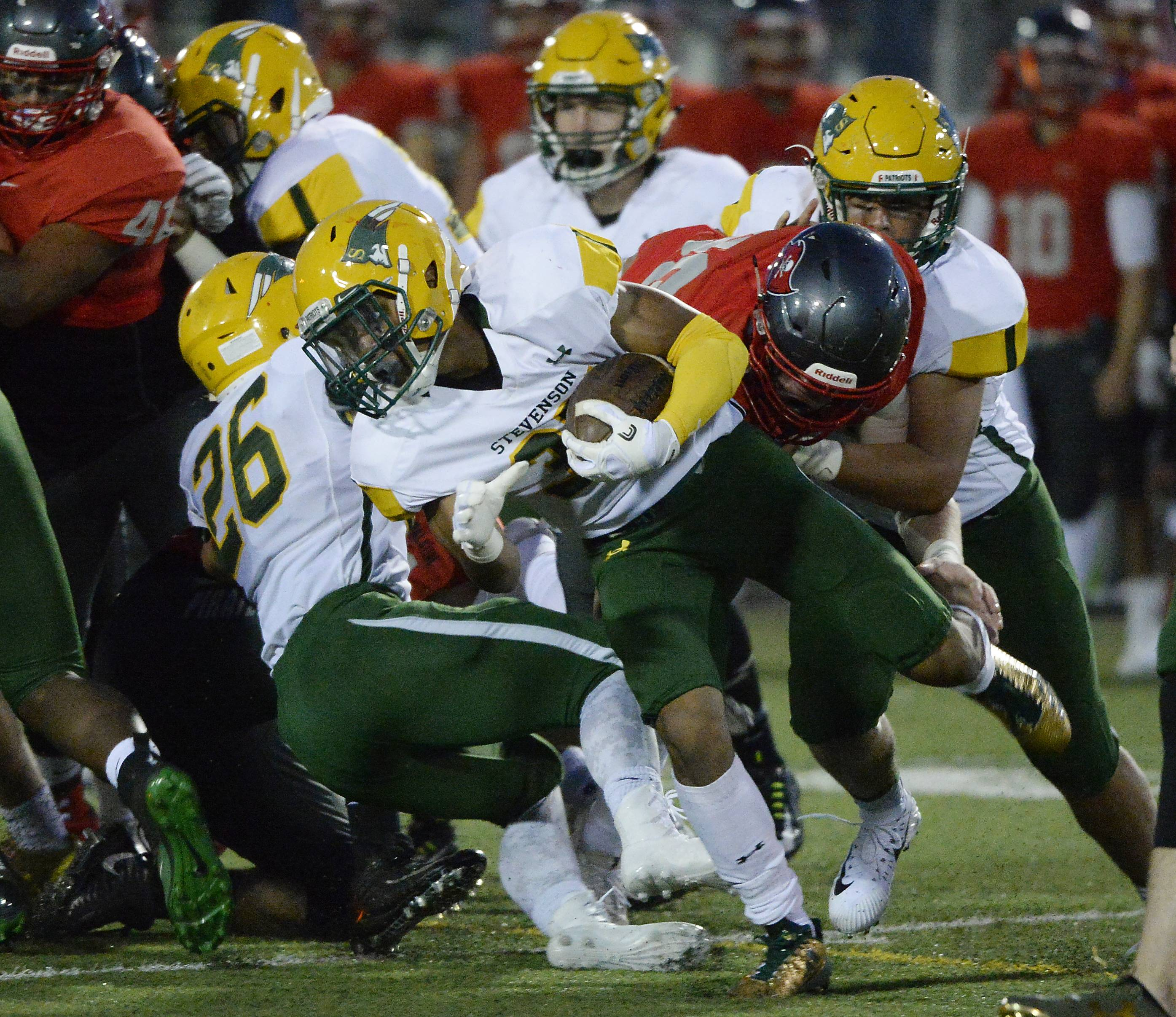 Stevenson's JeanMarc Etienne runs for short yardage in the first quarter against host Palatine on Friday.