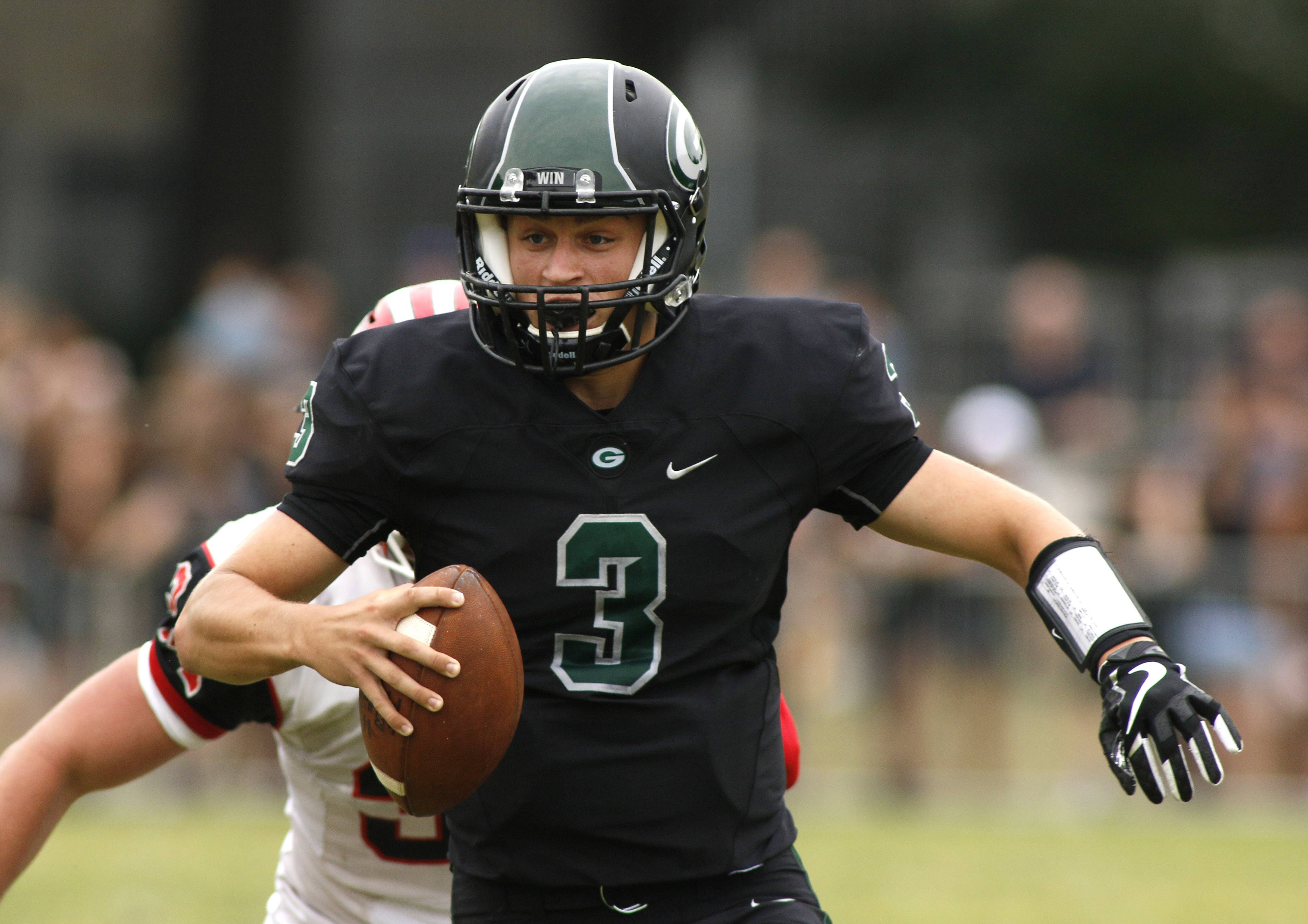 Glenbard West quarterback Alex Hollensbe scrambles for first-half yardage against Maine South.