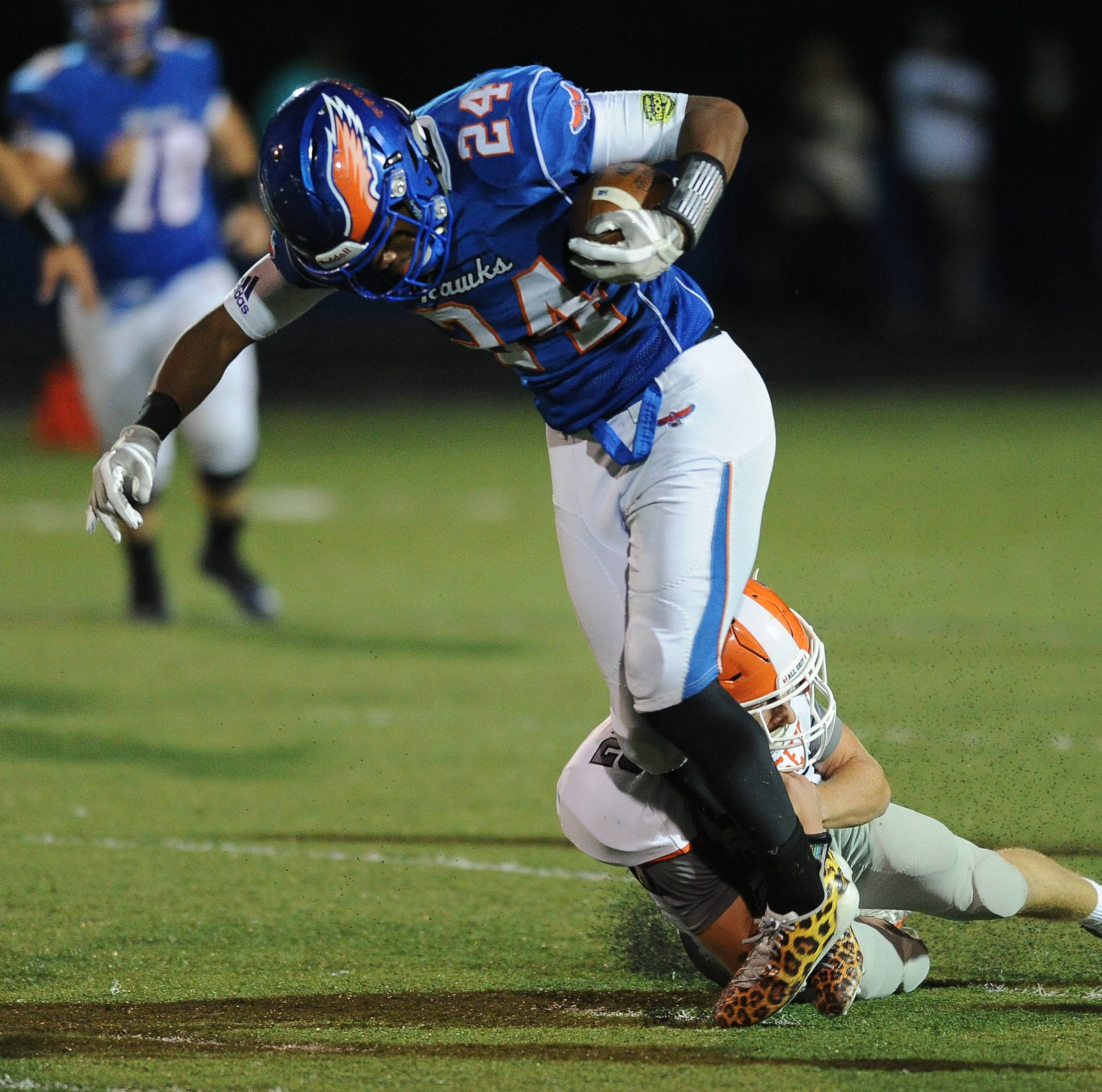 Hersey's Vince Carso wraps up Hoffman's Trevon Hall on a running play in the first half Friday at Hoffman Estates.