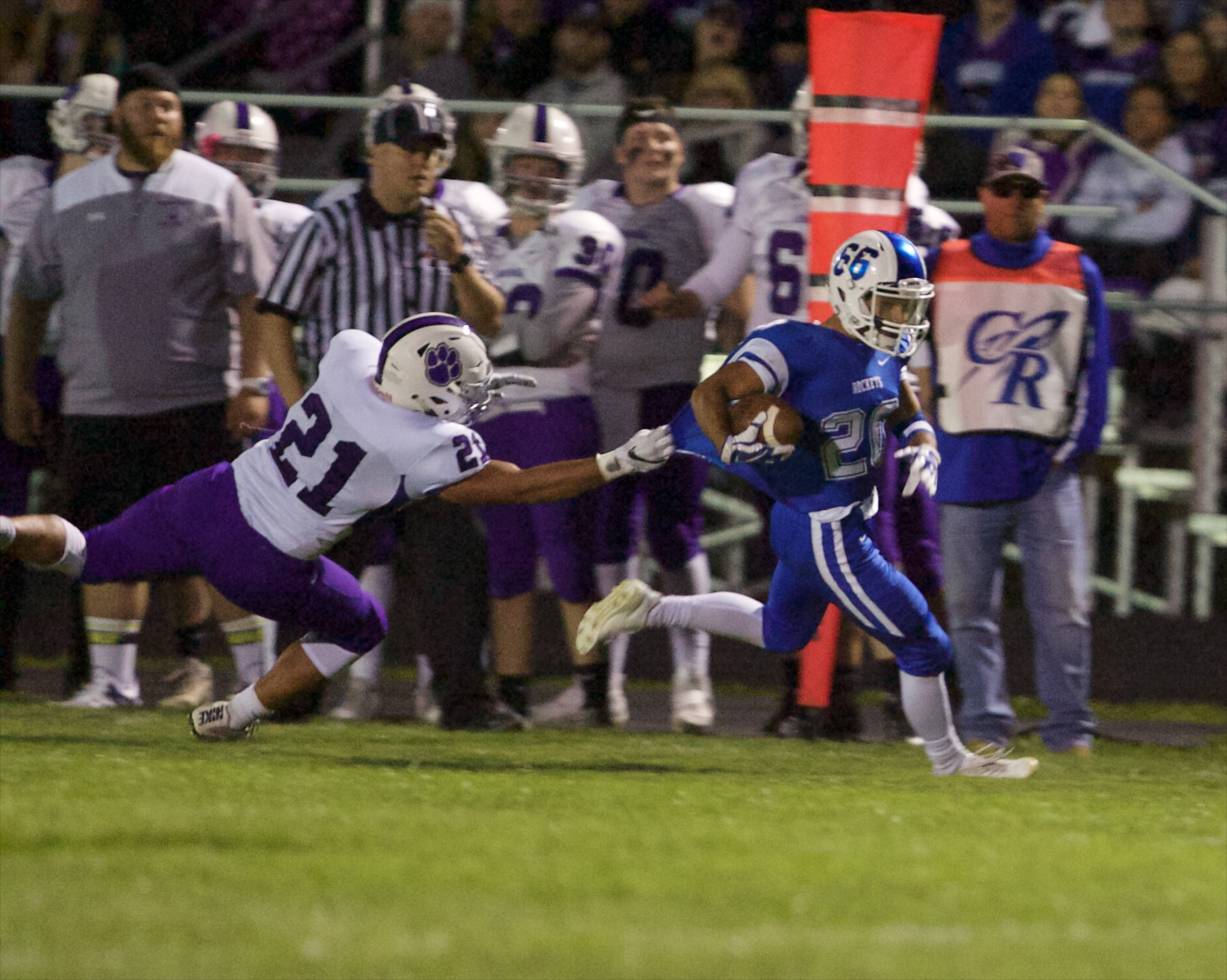 Burlington Central's Sawyer Perry gains yardage as Hampshire's Mohamed Harraz tries for the tackle Friday in Burlington.
