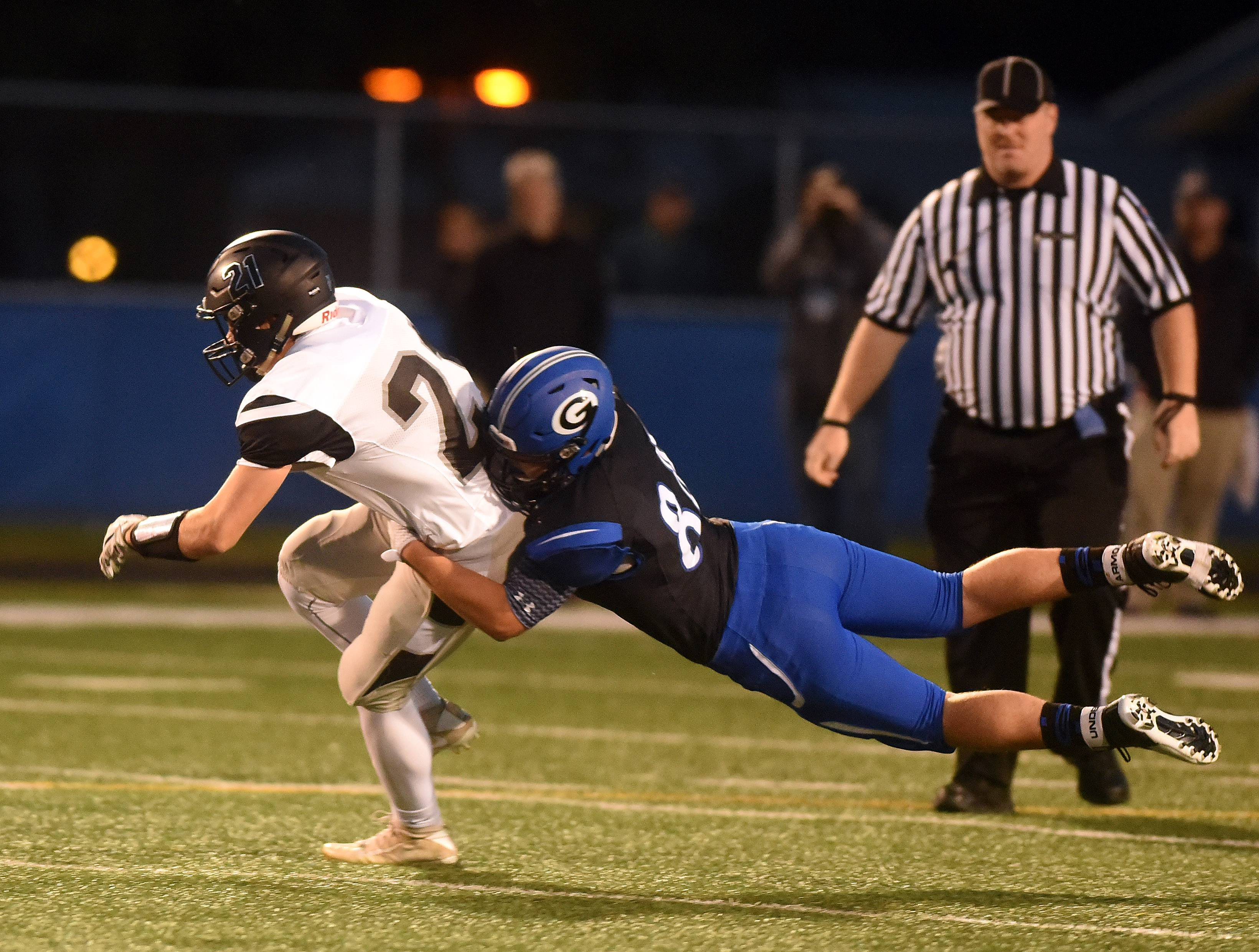 Kaneland's Alex Moses (21) is brought down by Geneva's Cory Marcinkus (84) during Friday's game in Geneva.