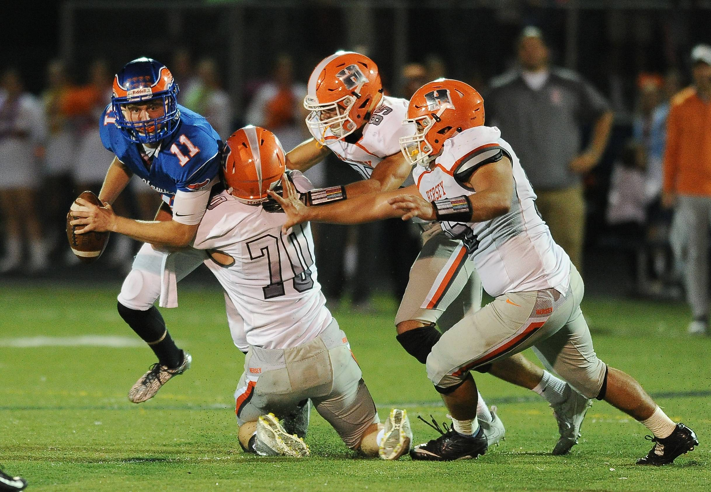 Hoffman Estates quarterback Austin Coalson fights off Hersey defenders in the first half Friday at Hoffman Estates.