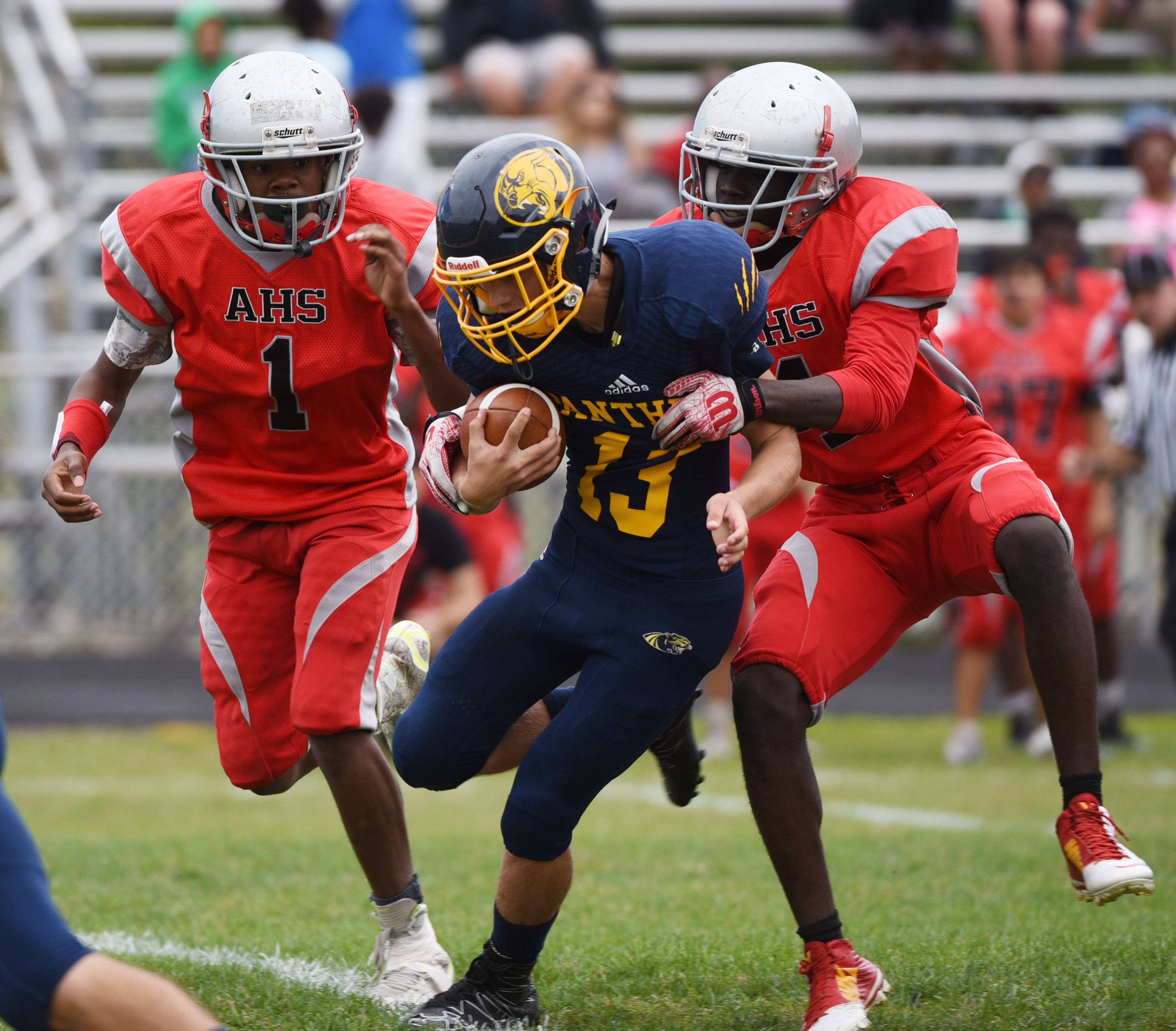 Round Lake quarterback Alex Larson rushes as Amundsen's Cameron Meredith, left, and Kennith Frimpong close in last Saturday.