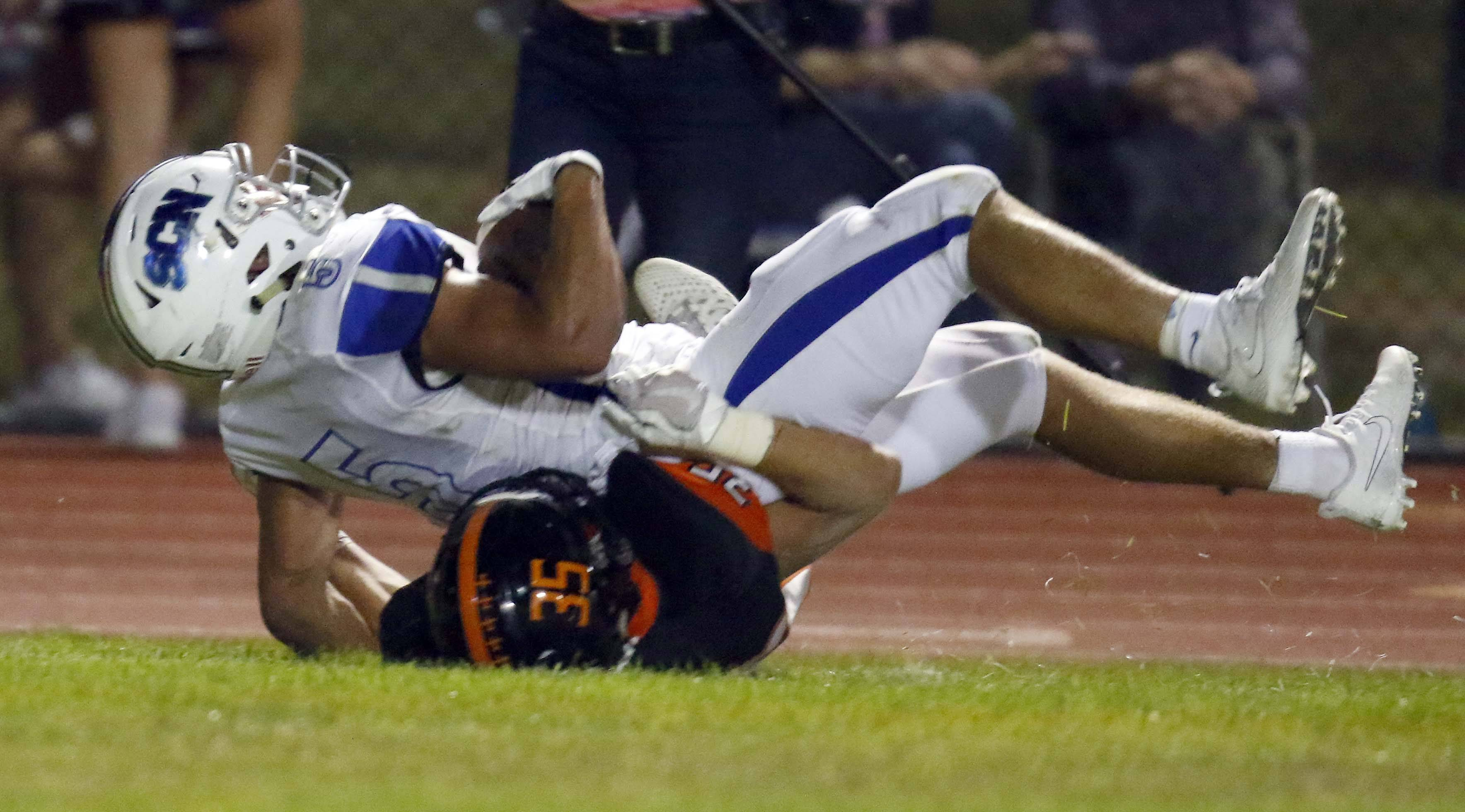 St. Charles North's Lucas Segobiano (5) rolls into the end zone over St. Charles East's Austin Klose (35) Friday during St. Charles North at St. Charles East football.