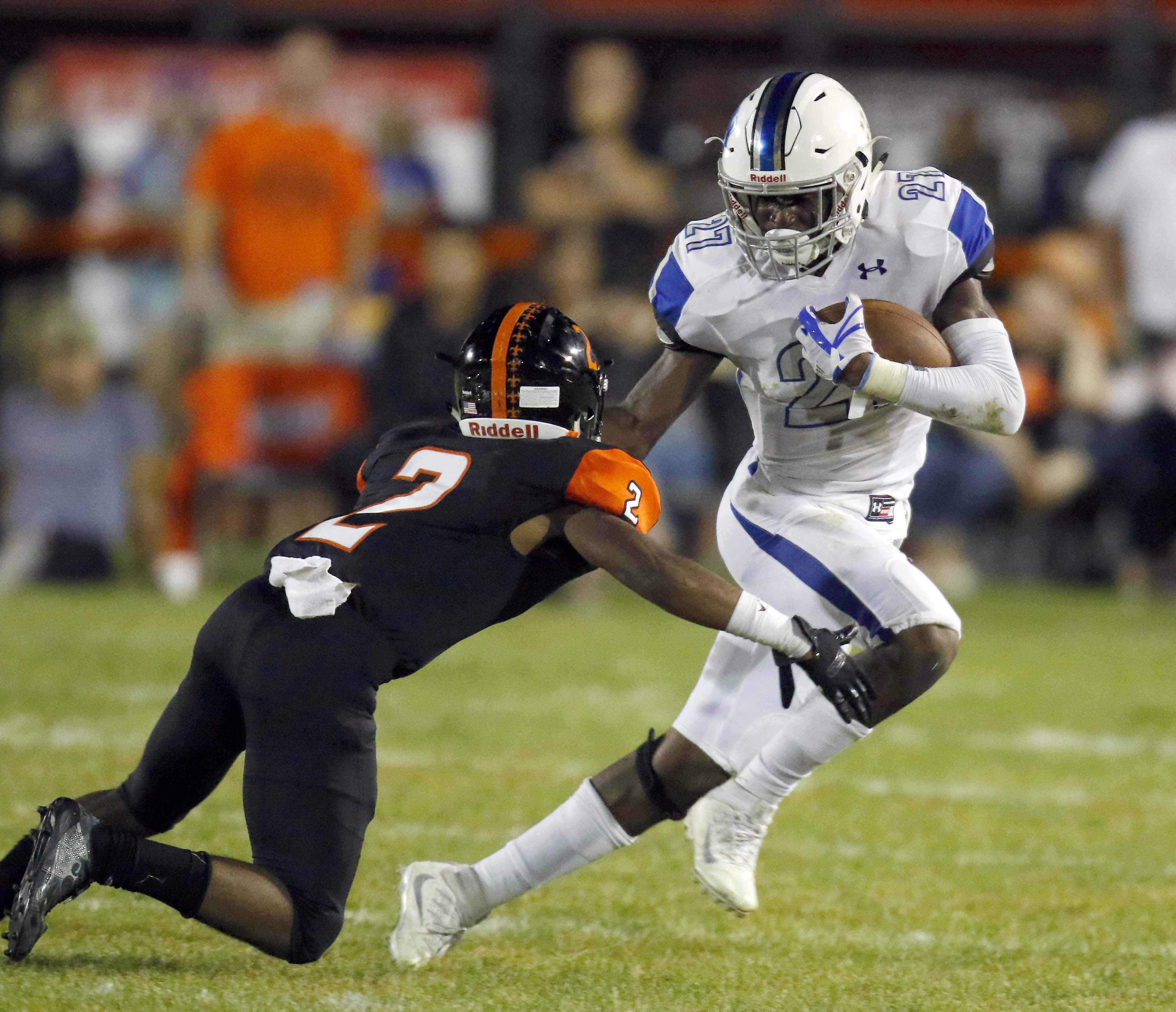 St. Charles North's Tyler Nubin (27) moves past St. Charles East's Yalon Rogers (2) Friday during St. Charles North at St. Charles East football.