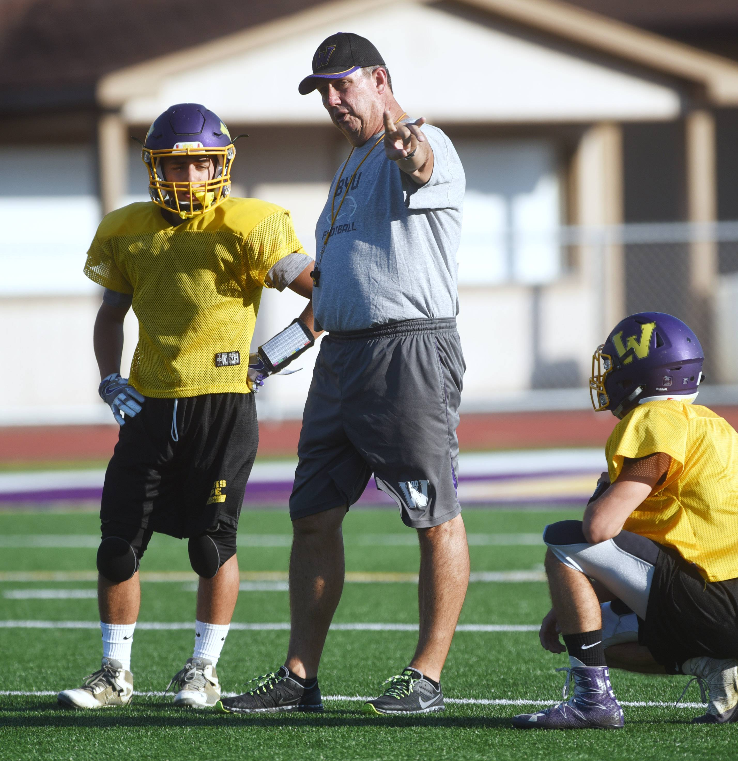Coach Dave Mills, center, works with his players during Wednesday's practice as Wauconda's football family sticks together through trying times.