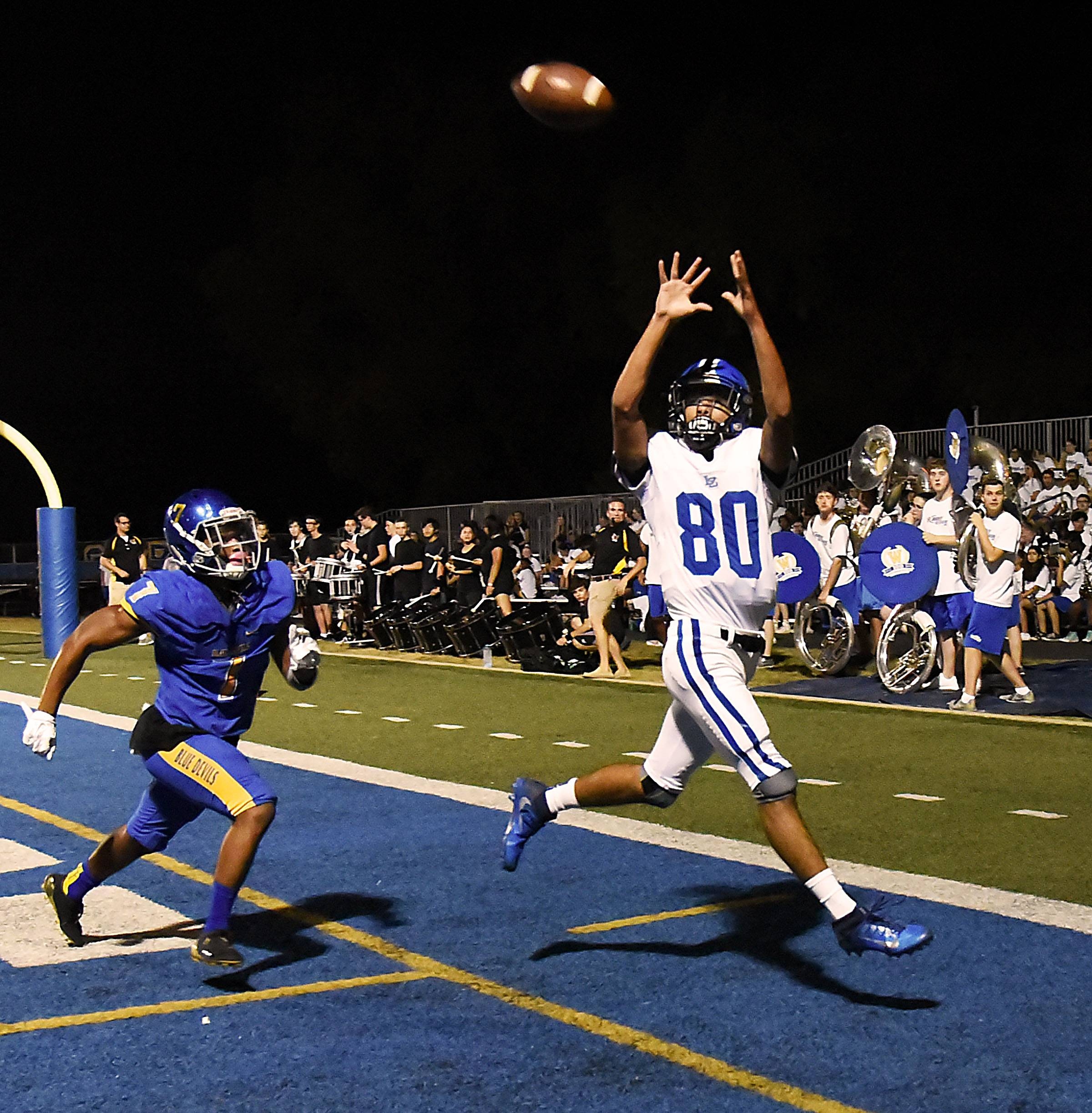 Lake Zurich's Payton Powell catches one of his 4 touchdown passes as Warren's Tavi Dungee defends on Friday in Gurnee. See story on Page 8.