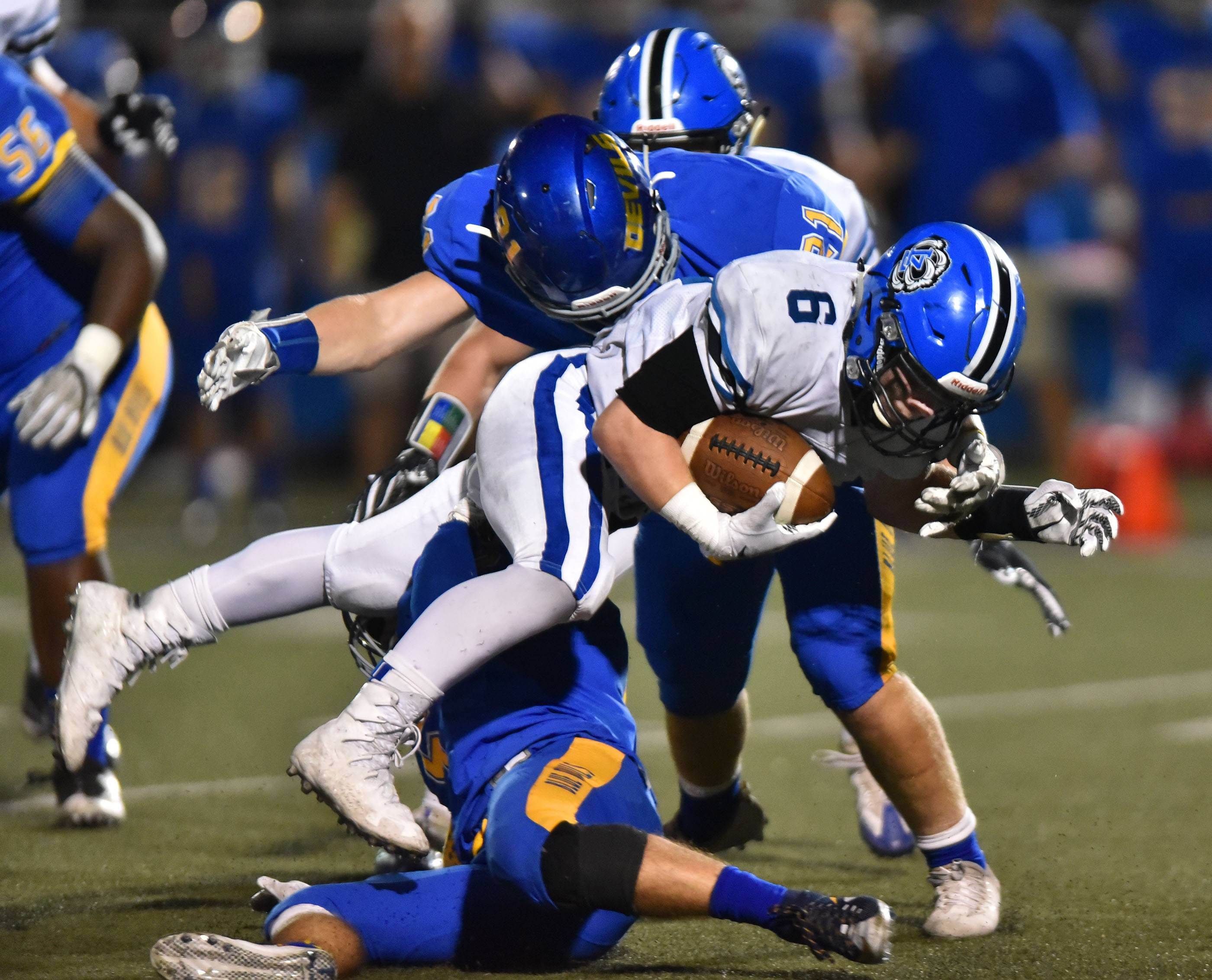 Lake Zurich's Joey Stutzman is tripped up by Warren's Caden Fox and Jared Keeter on Friday in Gurnee.