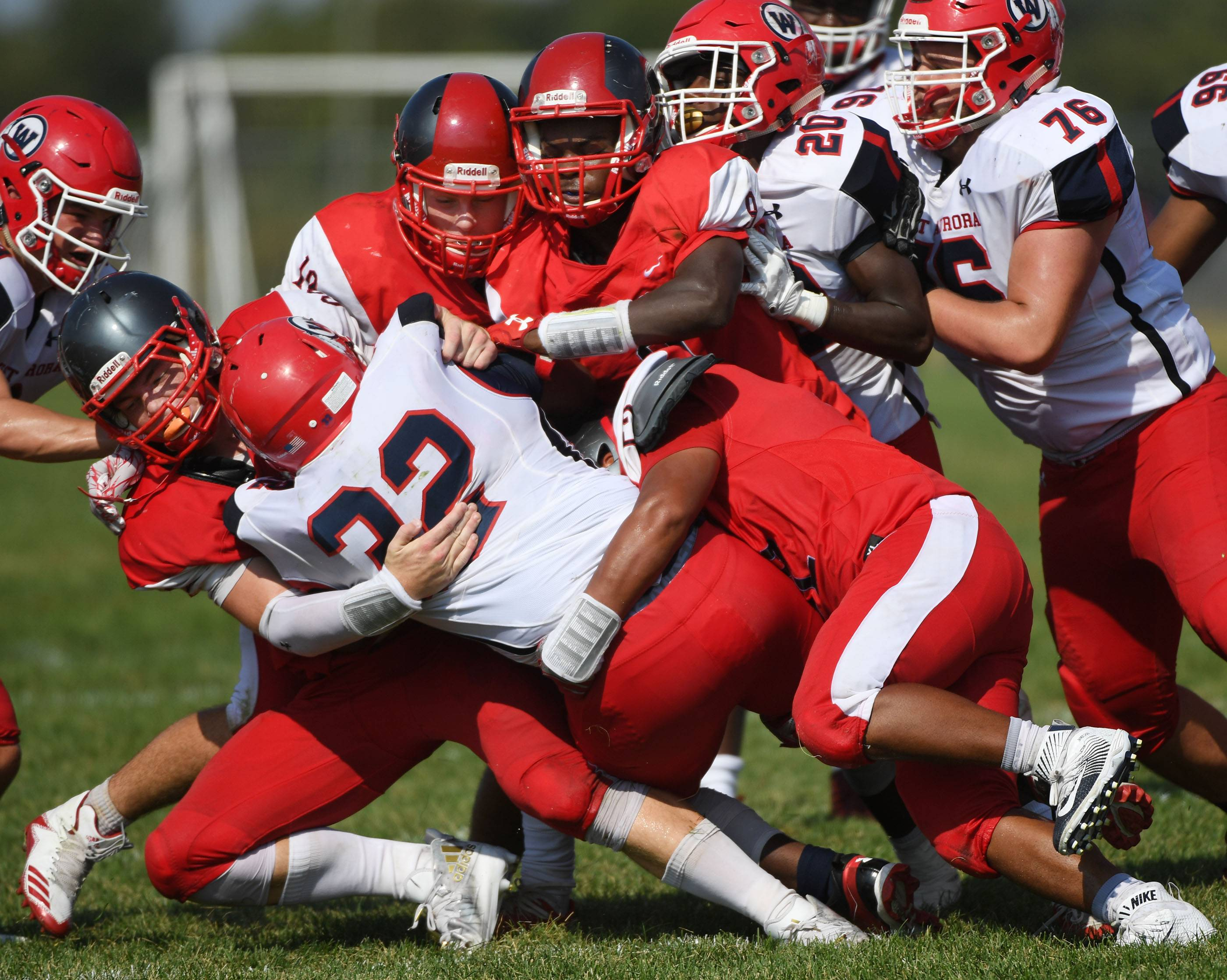Four South Elgin players bring down West Aurora's Trevon Tittle Saturday in South Elgin.