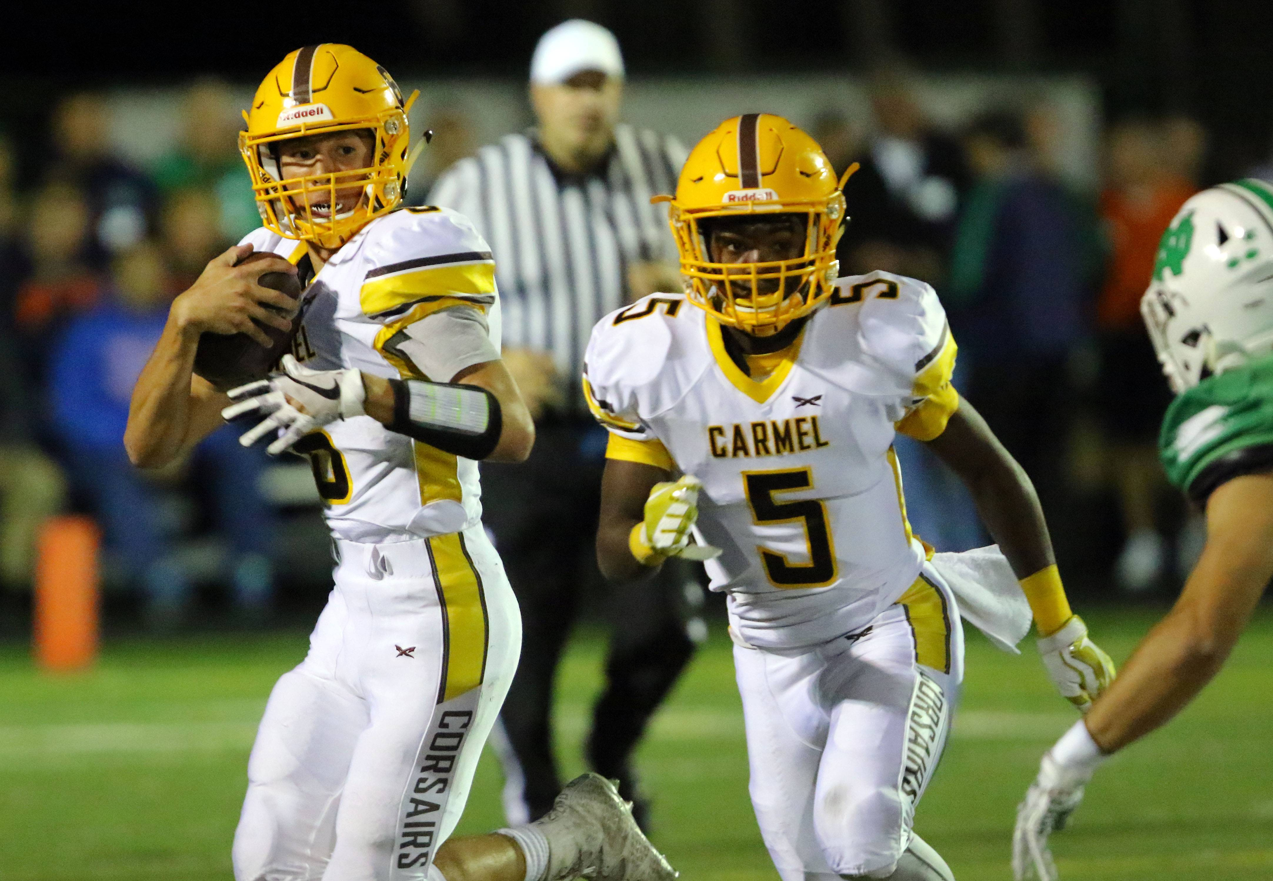 Carmel's Nick Fisher, left, returns a kickoff as Myles Tramill blocks against Notre Dame on Friday night in Niles.
