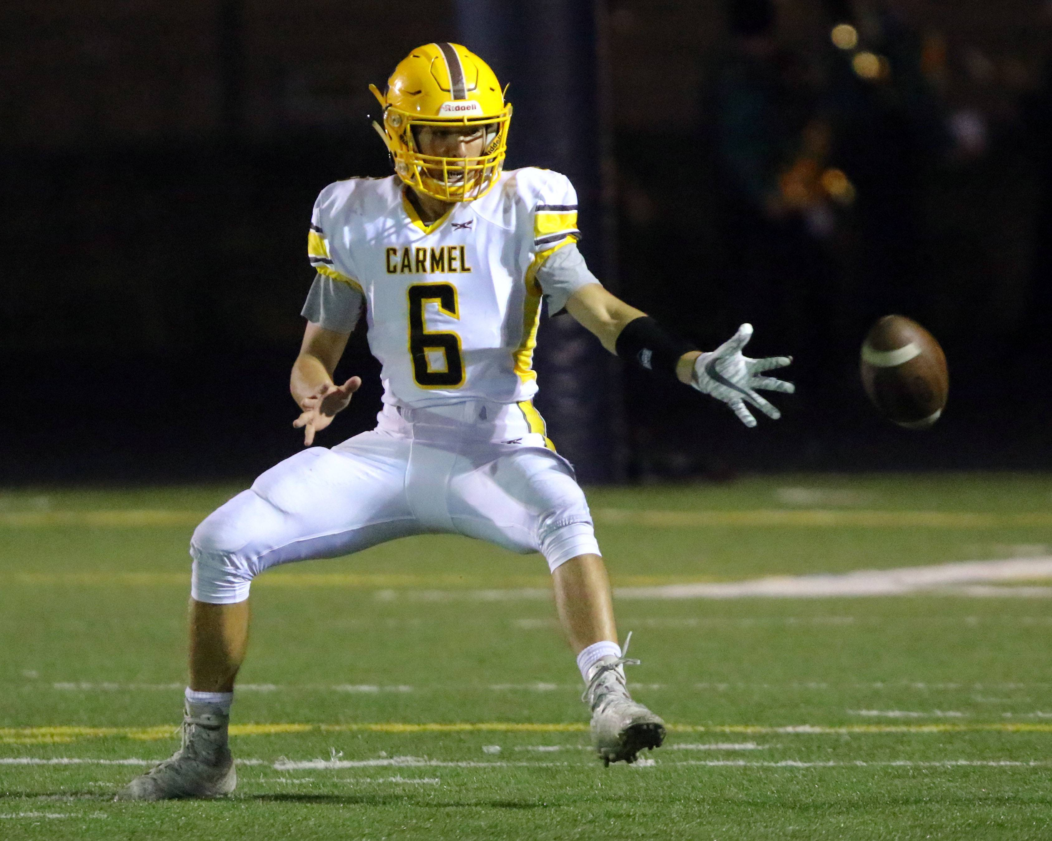 Carmel's Nick Fisher tries to field a kickoff against Notre Dame on Friday night in Niles.
