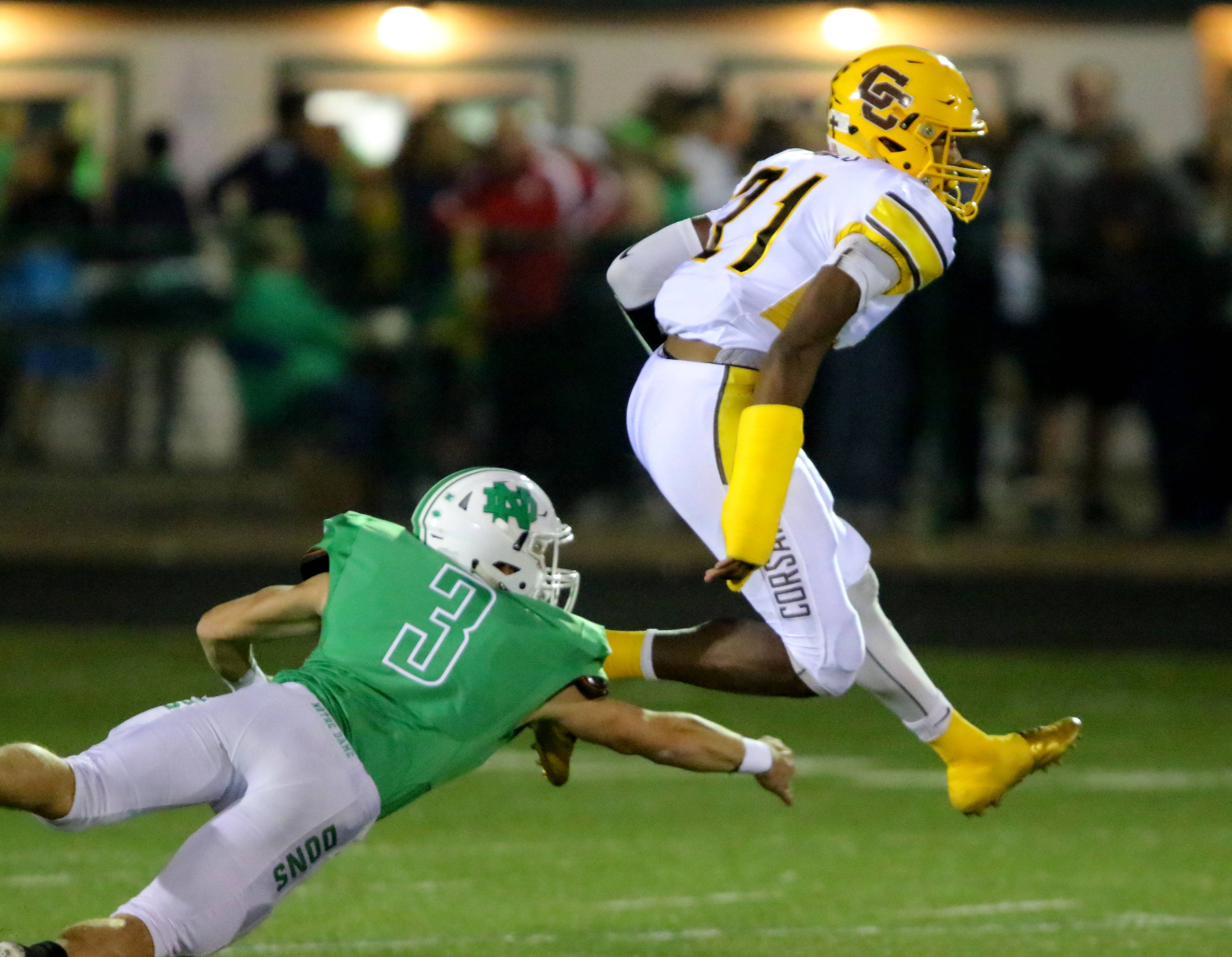 Carmel's Zaire Barnes, right, jumps over Notre Dame's Jake Martin on Friday night in Niles.