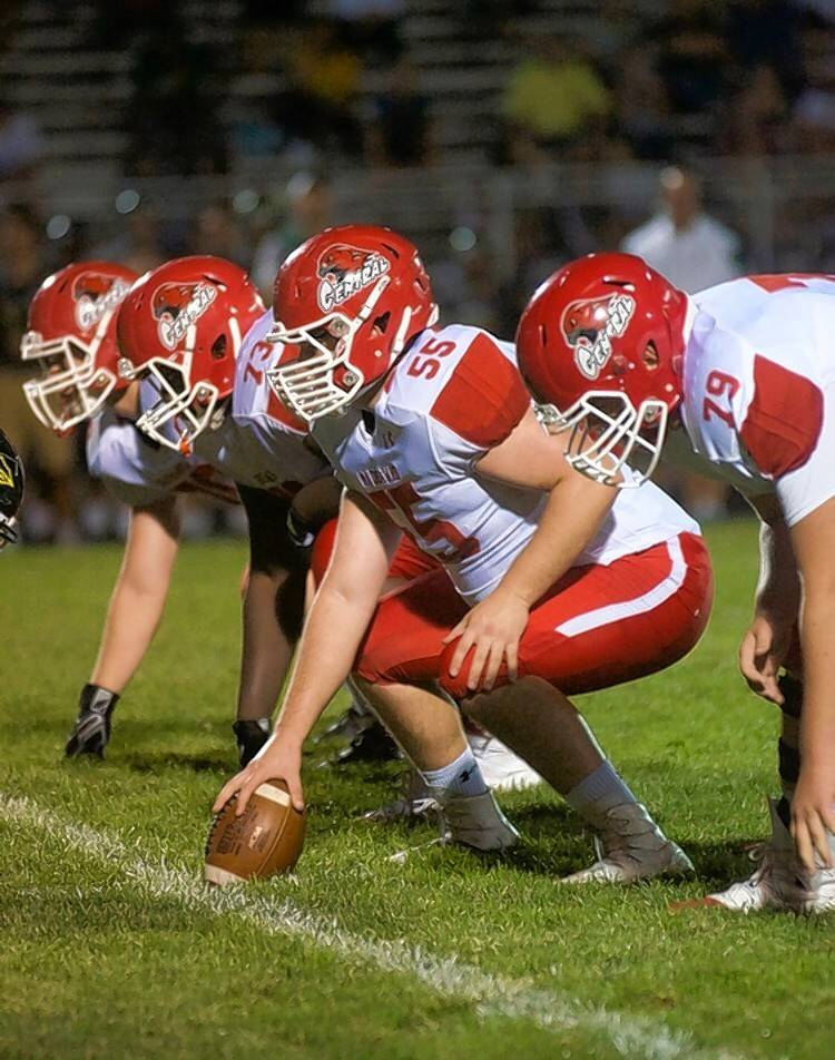 Naperville Central center Joe Kennedy (55) and his teammates take on cross-town rival Naperville North on Friday night.