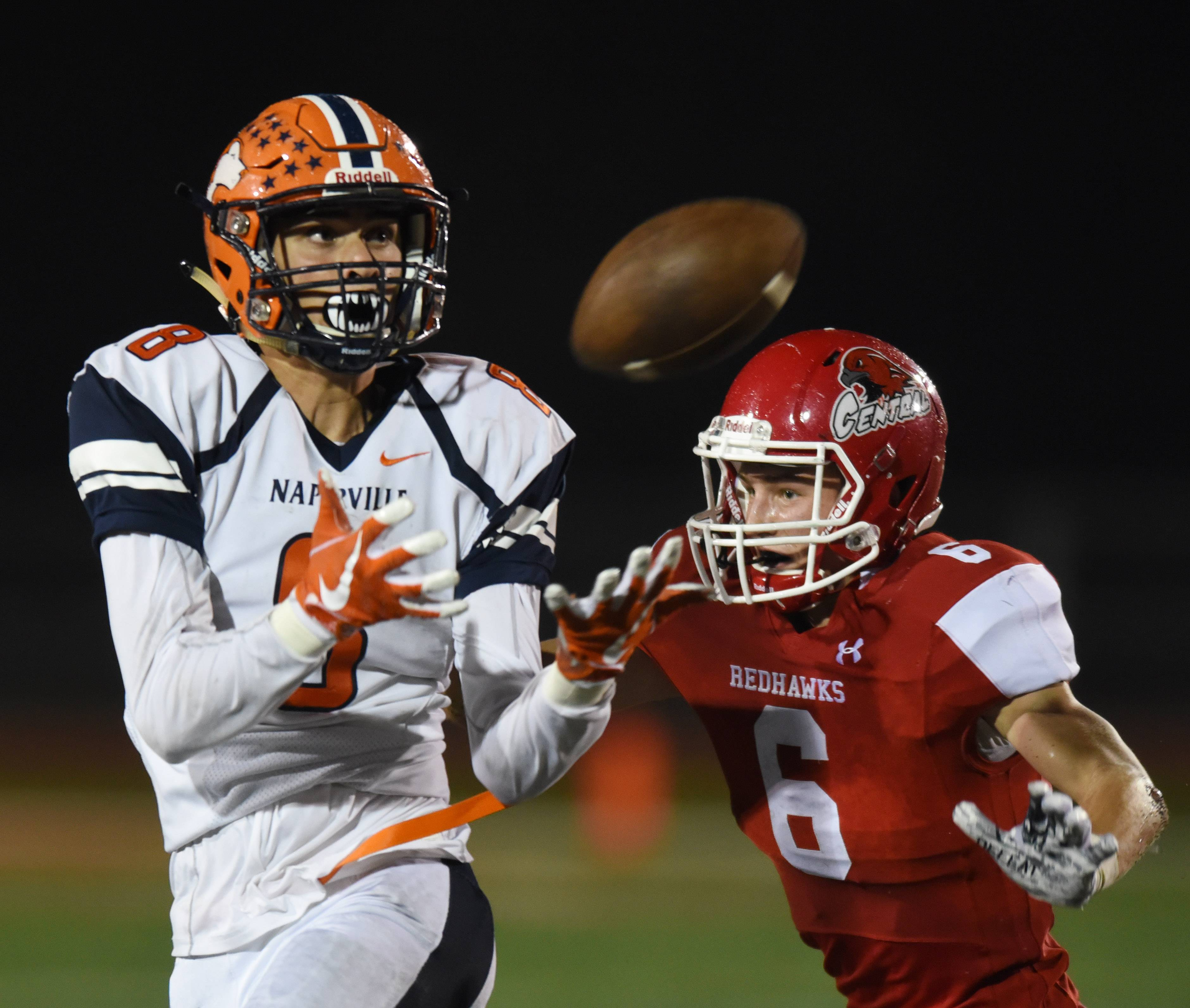 Naperville North's Nick Calcagno, left, catches a pass in front of Naperville Central's Branden Lindmark at Benedetti-Wehrli Stadium in Naperville Friday.