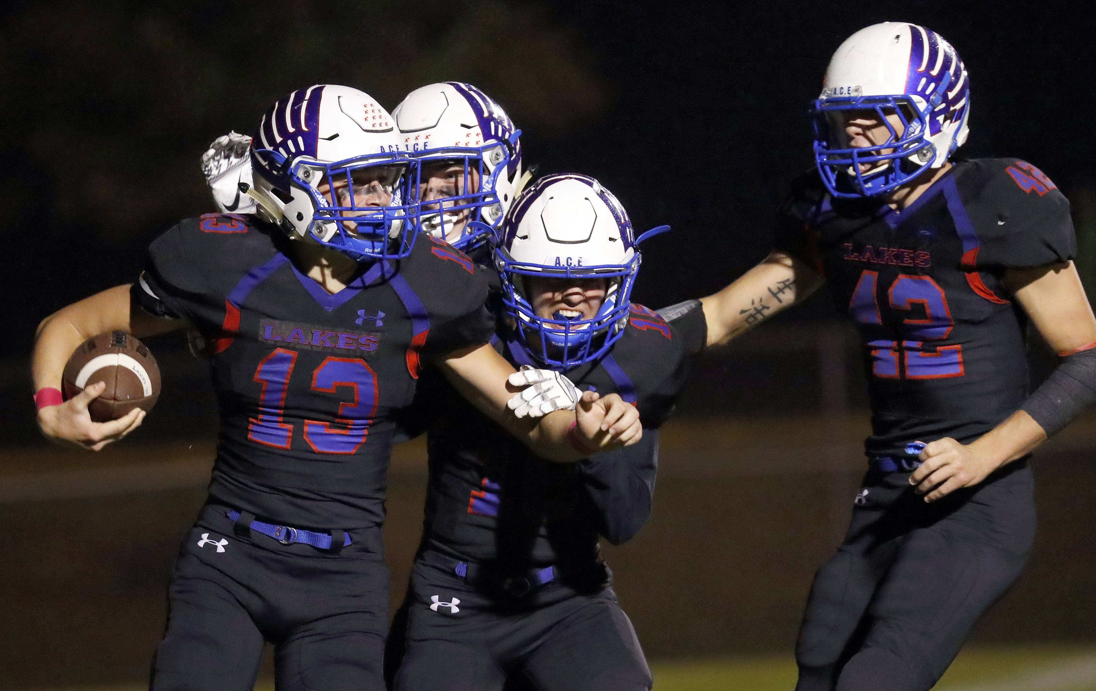Lakes' players celebrate with Chance Hoeller (13) after he returned a fumble for a touchdown against visiting Antioch on Friday night.