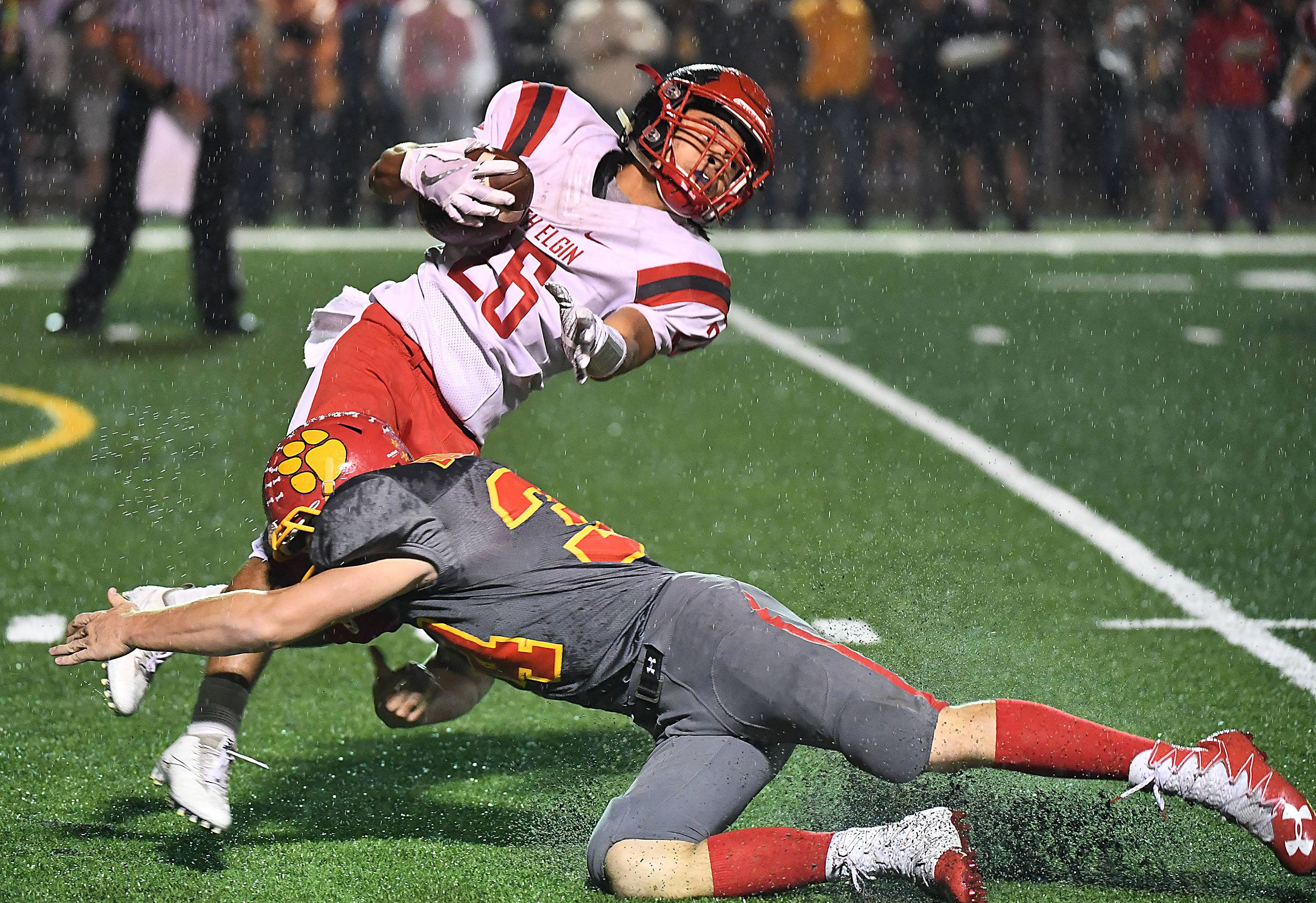 South Elgin's Jaron Wells is brought down by Batavia's Quin Urwiler Friday in Batavia.