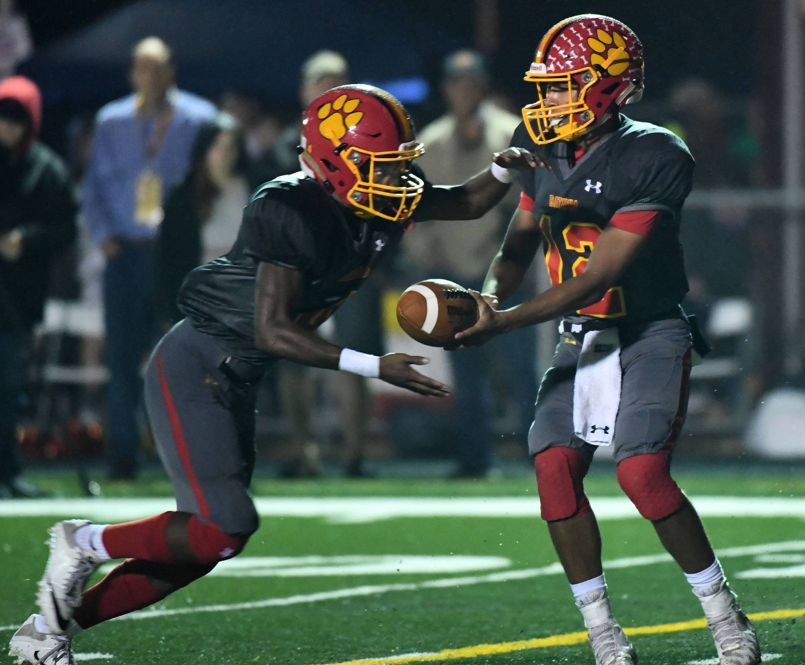 Batavia's Riley Cooper hands off to Reggie Phillips, who takes it to the one yard line against South Elgin in the first half Friday in Batavia.