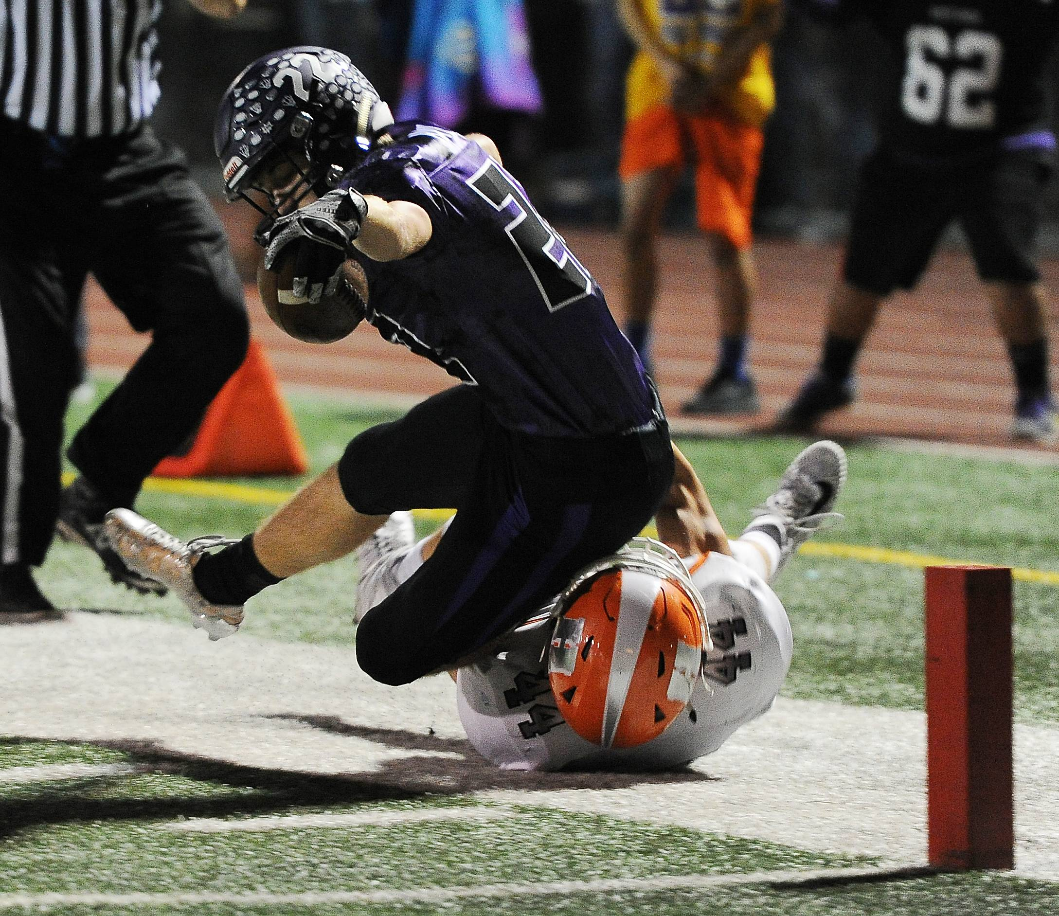 Rolling Meadows' Jared Axelrad reaches out on a touchdown attempt, but Hersey's Colton Kamysz stops him short in the first half at Rolling Meadows on Friday.