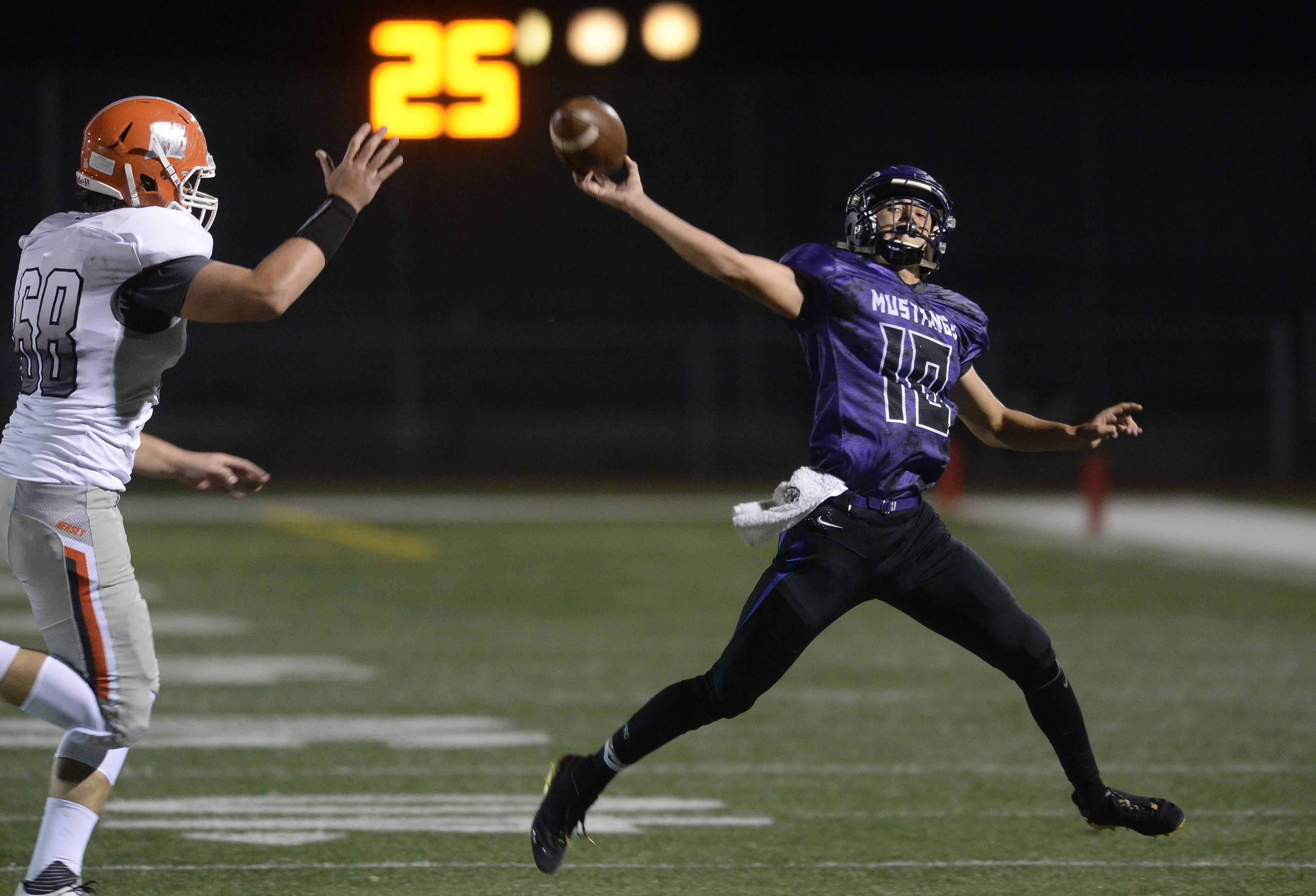Rolling Meadows quarterback Arek Kleniuk delivers a pass under duress in the first half against Hersey at Rolling Meadows on Friday.