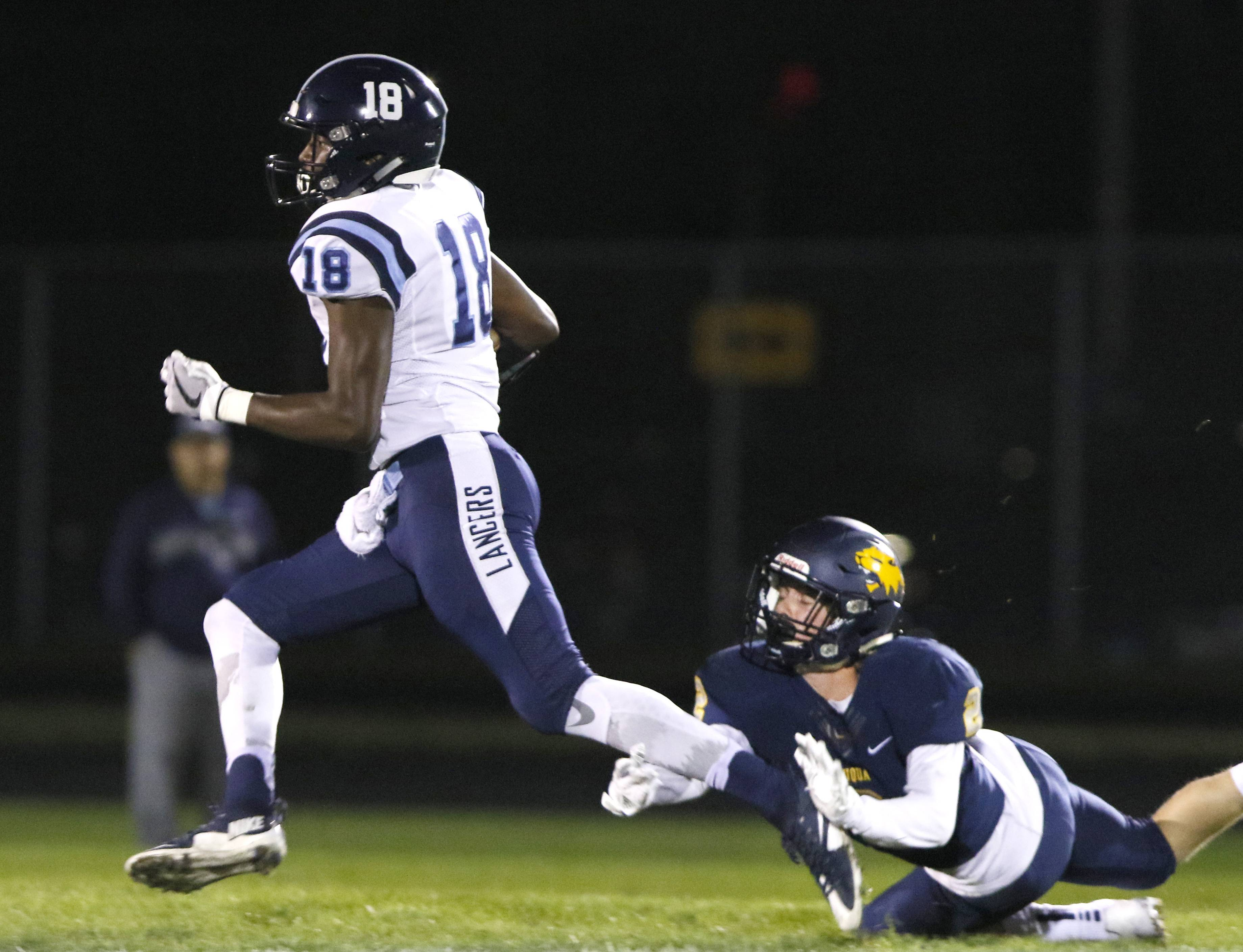 Lake Park's Keonta Nixon (18) runs for a touchdown after his catch against Neuqua Valley during Friday night football action in Naperville. Neuqua Valley's Ryan Wheeler makes a diving effort on the play.